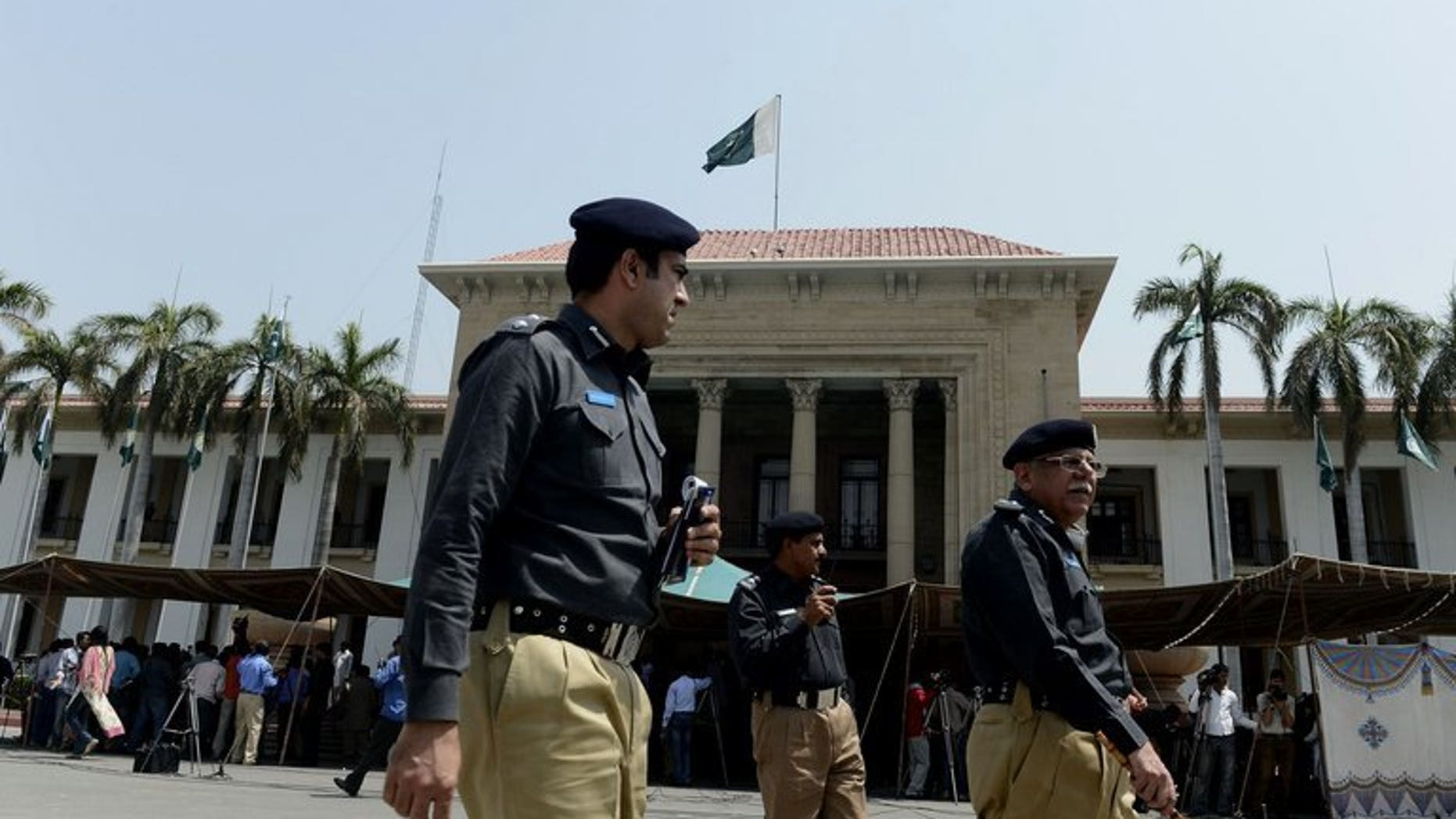 Pakistani police officers walk past Punjab provincial assembly building in Lahore on June 1, 2013. Police in Pakistan have arrested a cook on suspicion of murder after 22 members of a powerful landowning clan were poisoned in an alleged political feud with a rival branch of the family.