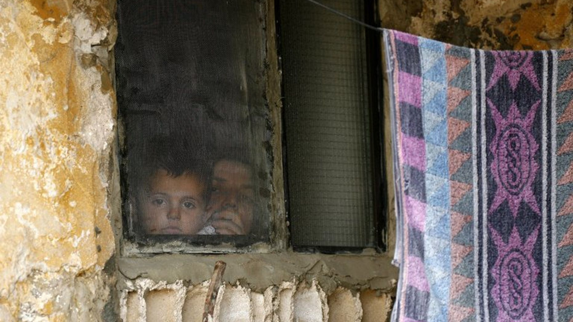 A Syrian woman and her child look out of a window at a refugee camp in the Lebanese town of Alman on June 20, 2013. Two Syrian refugee children in Lebanon suffocated to death overnight in a fire started by a lit candle during a power outage, Lebanon's state news agency reported on Friday.