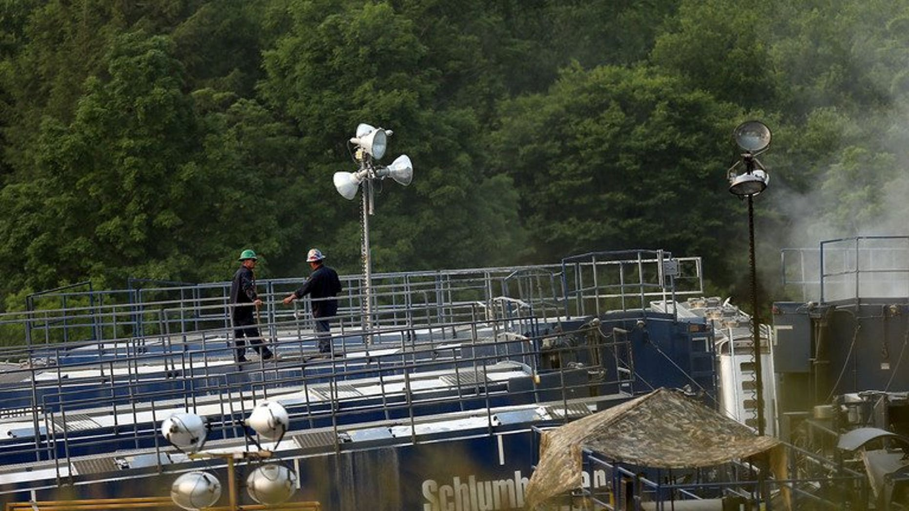 """Men work on a natural gas valve at a hydraulic fracturing site on June 19, 2012 in South Montrose, Pennsylvania. The government presented tax breaks for energy fracking companies to create the world's """"most generous"""" regime for shale gas extraction."""