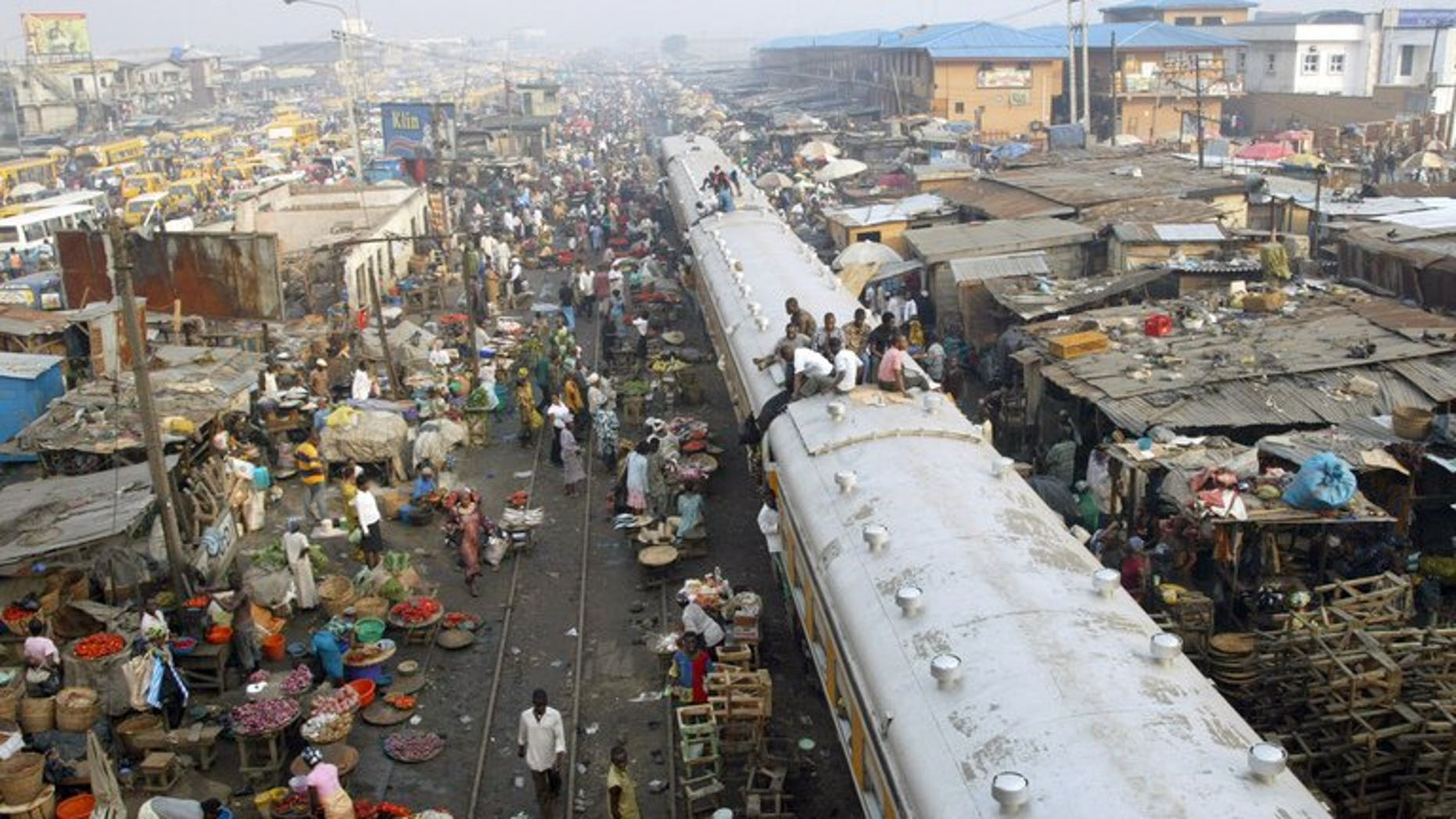 Commuters sit on coaches of a train chasing away vendors hawking their wares on the rail track in Oshodi district of Lagos on 16 November, 2007. A British national has been kidnapped by gunmen shortly after landing at the international airport in Lagos, Nigeria's largest city, a diplomat and a private security source told AFP Friday.