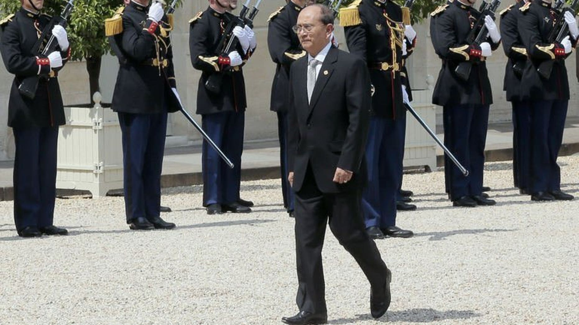 """Myanmar President Thein Sein passes by the French Republican Guards at the Elysee presidential palace on July 17, 2013 in Paris. Sein denied on Friday accusations of ethnic cleansing against Rohingya Muslims, saying the claims were part of a """"smear campaign"""" against his government."""