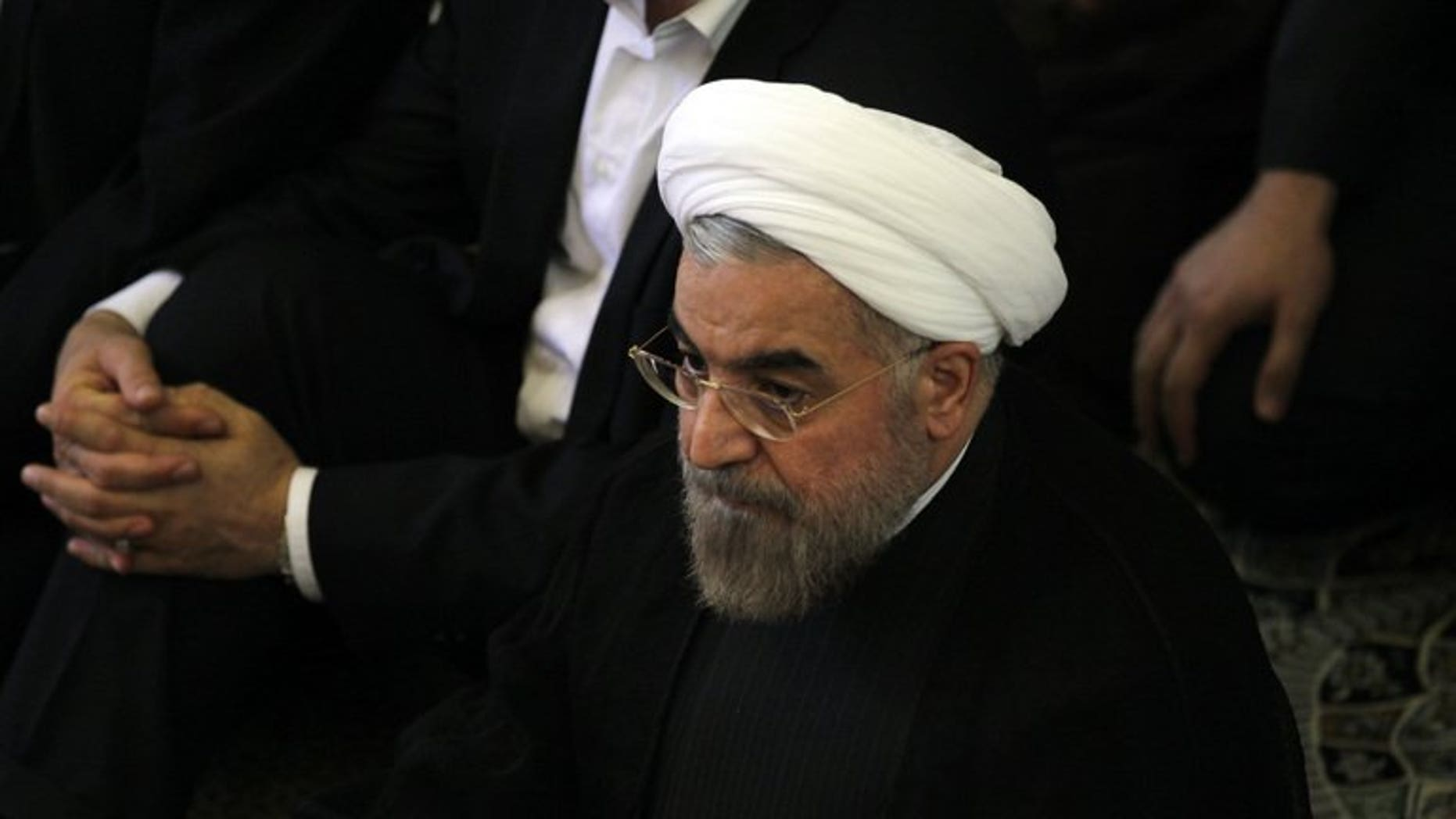 """Iranian president-elect Hassan Rowhani (C) attends the Friday prayer on July 12, 2013 in Tehran. World powers hope his election as president of Iran will provide fresh impetus and """"a change in tone"""" in ongoing talks on the country's controversial nuclear programme."""