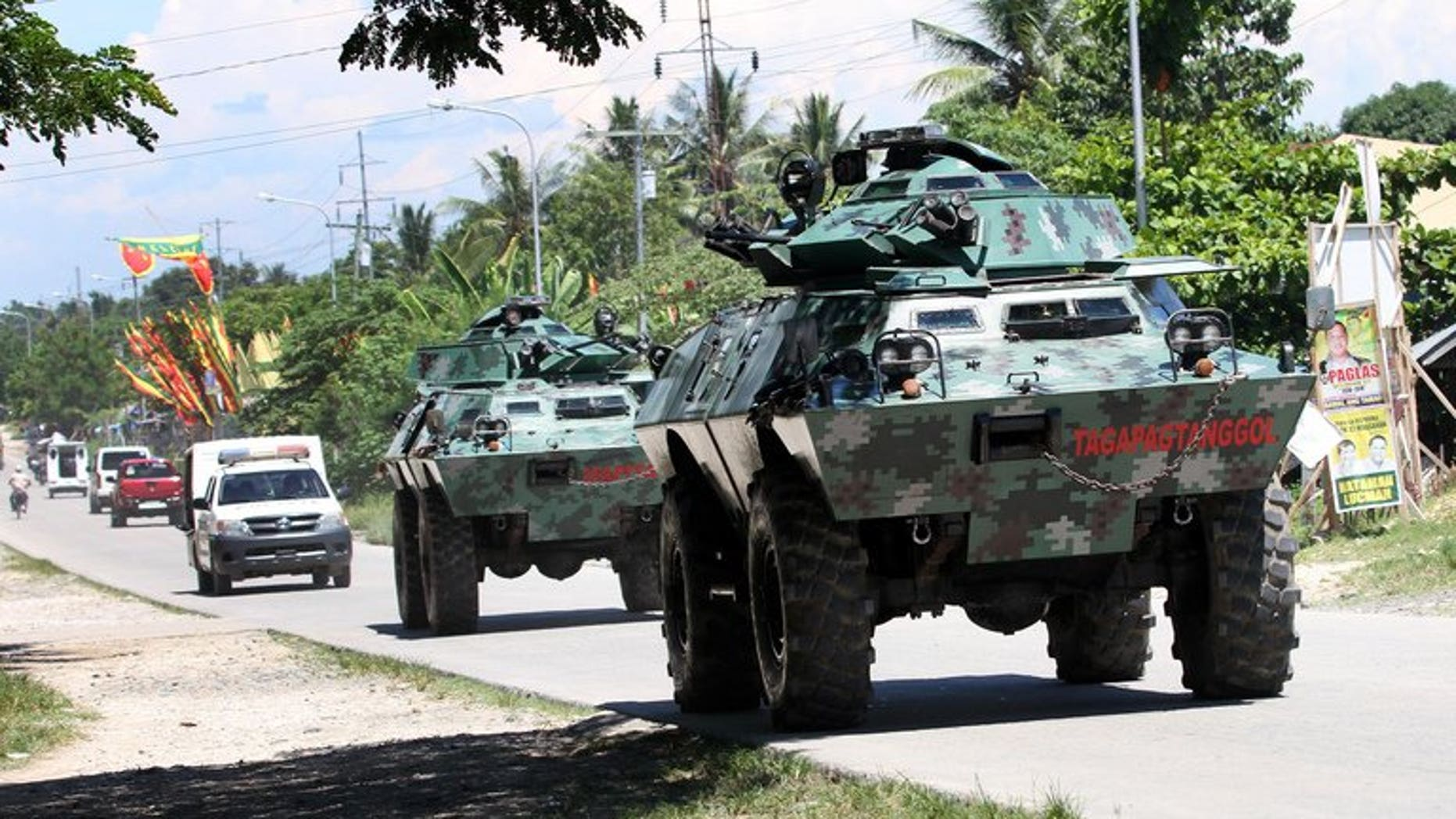 This photo taken on May 13, 2013 shows military armoured personnel carriers rumbling along a highway in Mindanao. Seven people were killed when communist insurgents attacked a rural army outpost there.