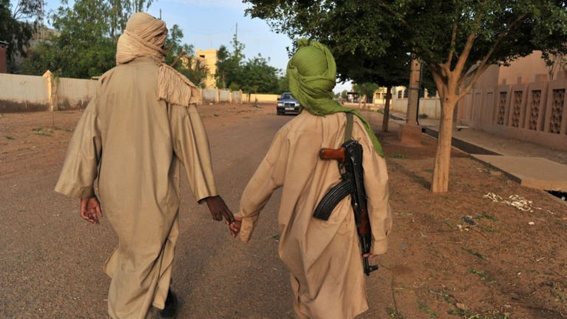 Two young fighters of an Islamist group walk in the streets of Gao city in Mali on July 17, 2012. Gunmen have abducted four polling staff and a local official in the northern Malian town of Tessalit, a week before a presidential poll meant to restore the country's unity, a local official said.