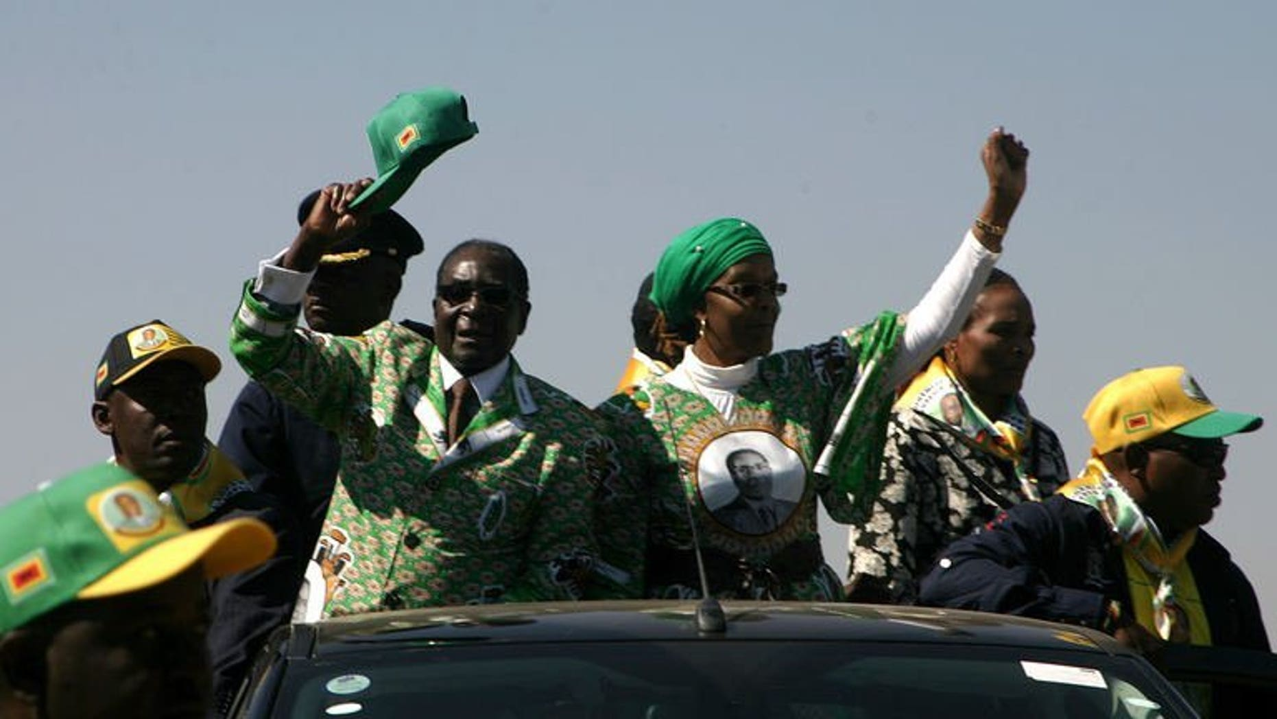 Zimbabwe's President Robert Mugabe (2nd L) waves as he arrives to address crowds gathered during an election campaign rally held at Chibuku Stadium, in Chitungwiza on July 16, 2013. Mugabe on Saturday warned South Africa's Jacob Zuma to stop his top mediator from commenting on the country's political crisis, as the veteran leader stepped up electioneering.