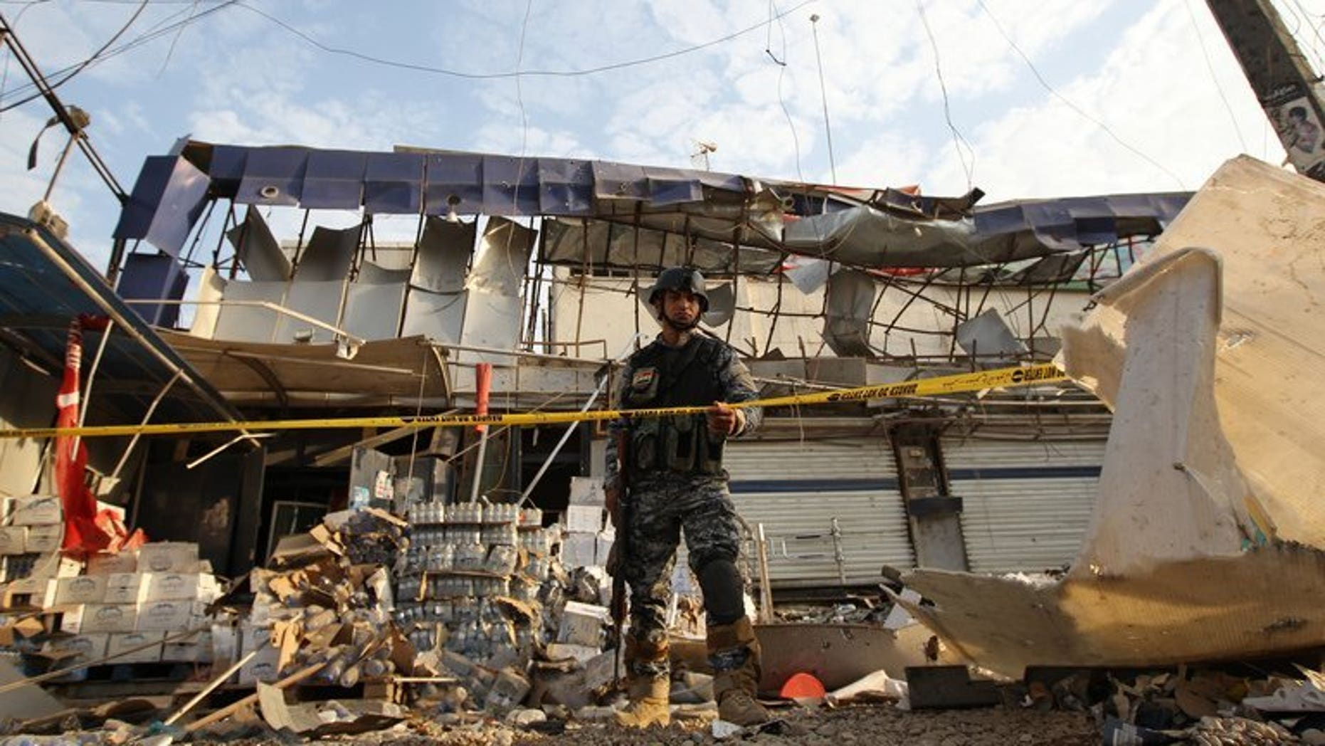 An Iraqi policeman inspects the damage outside a supermarket in central Baghdad's commercial Karrada neighbourhood on June 25, 2013. At least 22 people were killed in a string of car bomb attacks on Saturday timed for nightfall when shoppers take to the streets during Ramadan, security and medics said.