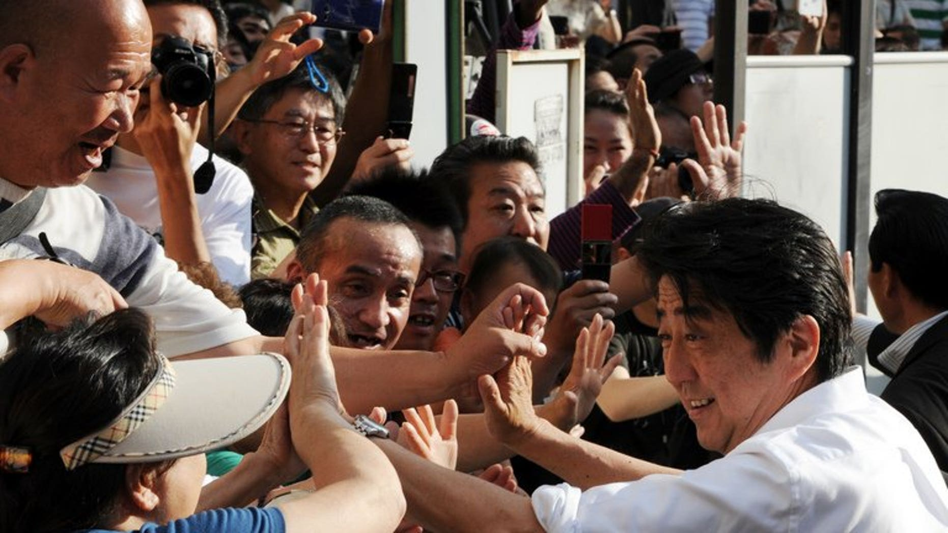 Japanese Prime Minister and ruling Liberal Democratic Party leader Shinzo Abe (R) greets supporters in Tokyo on July 20, 2013. Japanese voters go to the polls Sunday in an election expected to strengthen Abe's hand, potentially giving him power to push much-needed economic reforms.