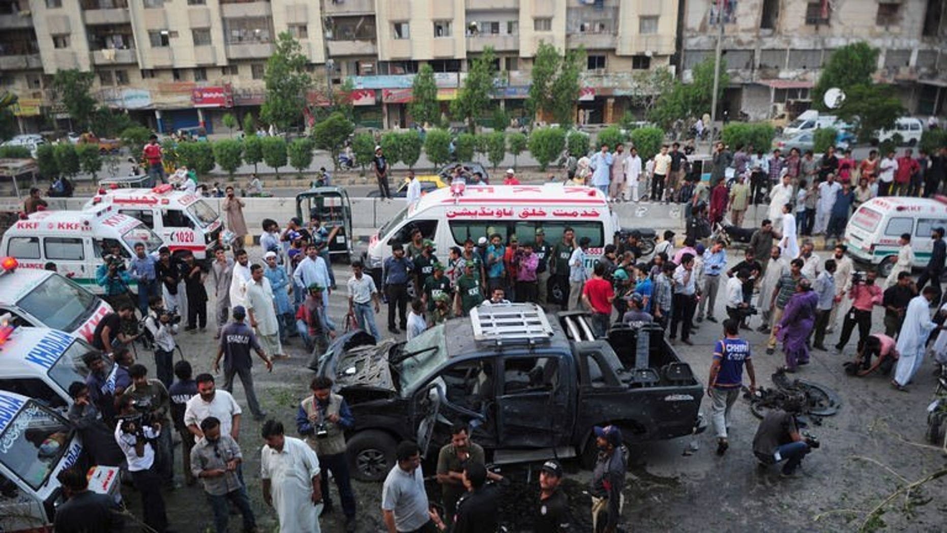 Pakistani security personnel collect evidence at the site of a bomb attack in Karachi on July 20, 2013. Two separate bomb explosions late Saturday killed four people and wounded seven others in Pakistan's port city Karachi, police said.