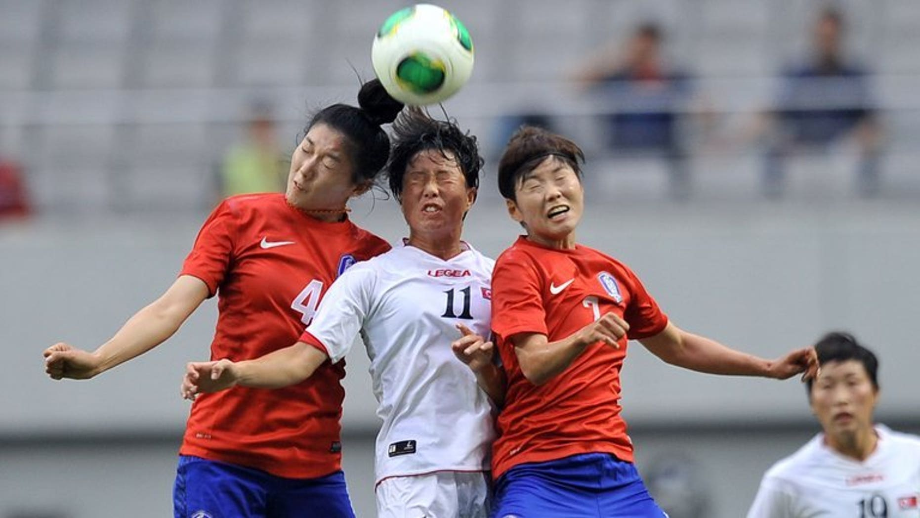 North Korea's Ri Ye-Gyong (centre) competes with South Korea's Shim Seo-Yeon (left) and Jeon Ga-Eul (right) during the Women's East Asian Cup football match in Seoul on July 21, 2013. North Korea won the match 2-1.