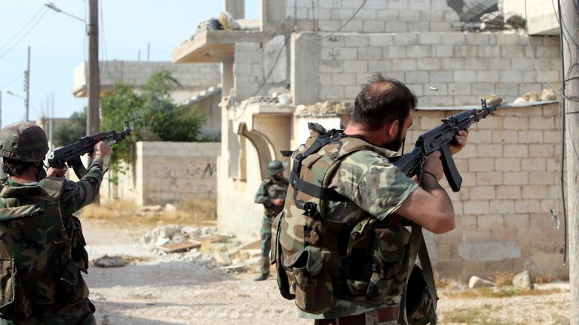 Syrian soldiers fire their weapons during a battle against opposition fighters in Qusayr, on May 23, 2013. A Syrian pro-regime militia shot dead 13 members of the same family, including six children, in the Mediterranean coastal village of Bayda, according to the Syrian Observatory for Human Rights.