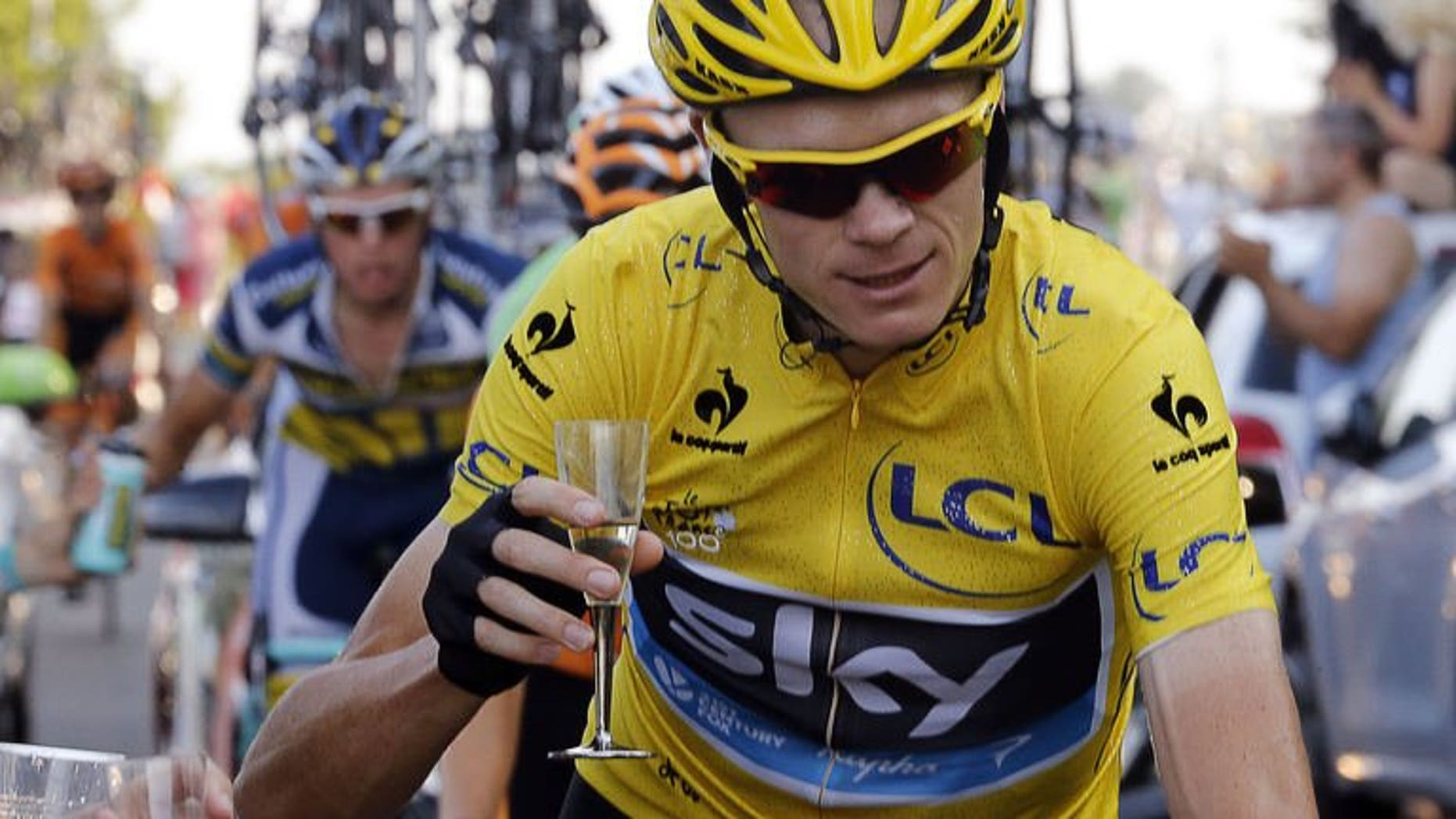 Overall leader's yellow jersey Britain's Chris Froome holds a glass of Champagne as he rides next to his team car, during the 133.5 km twenty-first and last stage of the 100th edition of the Tour de France cycling race on July 21, 2013 between Versailles and Paris. Froome was crowned champion of the 100th edition of the Tour de France.