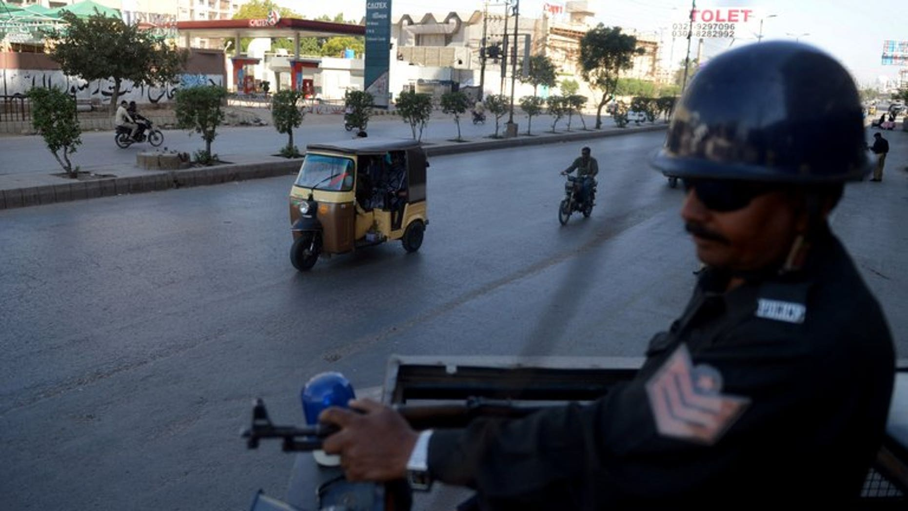 A Pakistani policeman stands guard on a police van in Karachi on February 8, 2013. A hand grenade attack targeting the office of a political party late Sunday killed at least two people and wounded six others in Pakistan's port city of Karachi, police said.