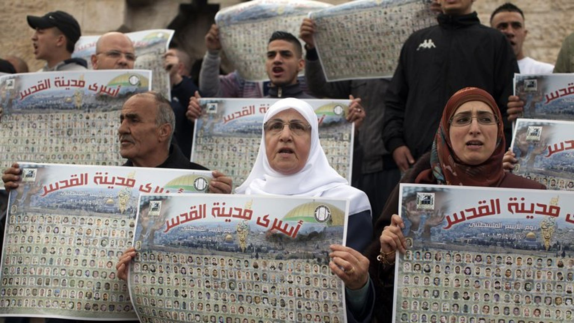Palestinians hold portraits of relatives jailed in Israeli prisons as they demand their release in the old city of Jerusalem on April 17, 2013. Israel is set to decide on the release of around 80 long-serving Palestinian prisoners ahead of renewed peace talks, an Israeli official said on Monday.