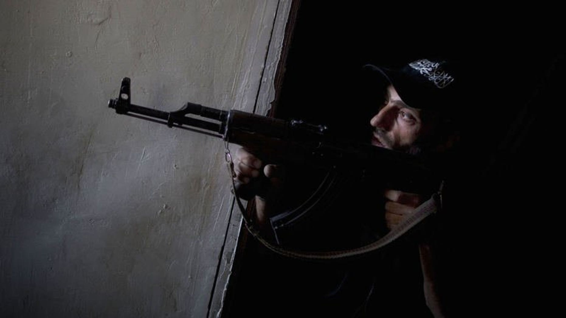 A Syrian rebel fighter points his gun towards pro-regime forces during clashes in the Salaheddine district of Aleppo, on July 9, 2013. Syria's rebels have seized the strategic town of Khan al-Assal, a regime bastion situated in the northern province of Aleppo, according to the Syrian Observatory for Human Rights.