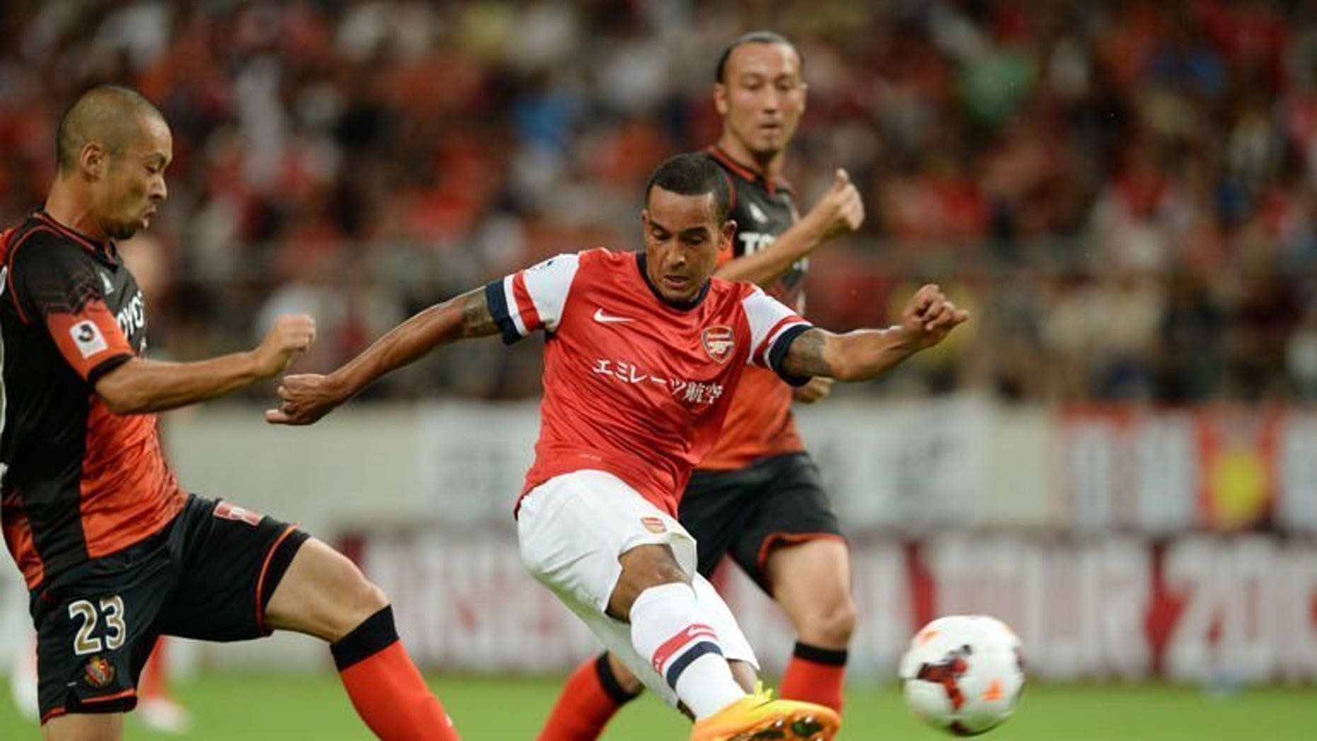Arsenal forward Theo Walcott (C) shoots towards goal between Nagoya Grampus defenders during their friendly in Toyota, Japan's Aichi prefecture on July 22, 2013. French striker Olivier Giroud struck his sixth goal in three Asian tour games as Arsenal marked manager Arsene Wenger's return to his former club Grampus with a 3-1 win on Monday, with England's Walcott adding a third after half-time.