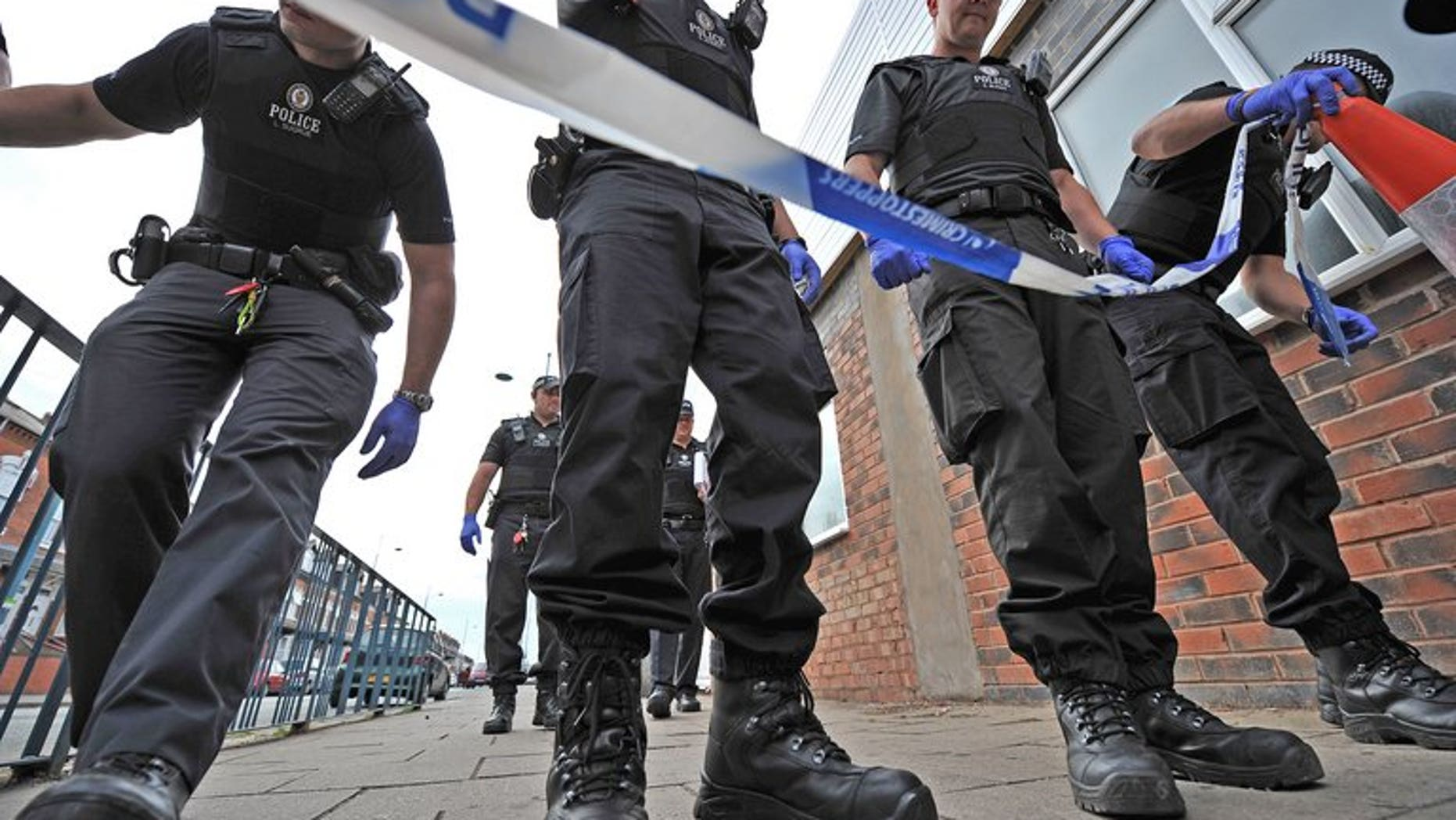 """Police officers search a crime scene in Birmingham on August 10, 2011. British police on Monday charged a Ukranian man with the """"terrorist-related"""" murder of an elderly Muslim man who was walking home from a mosque."""