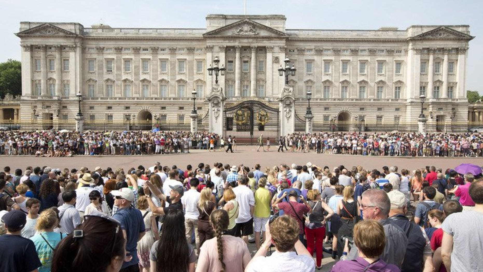 Crowds of tourists gather on the steps of the Queen Victoria Memorial Statue outside Buckingham Palace in central London on July 22, 2013.