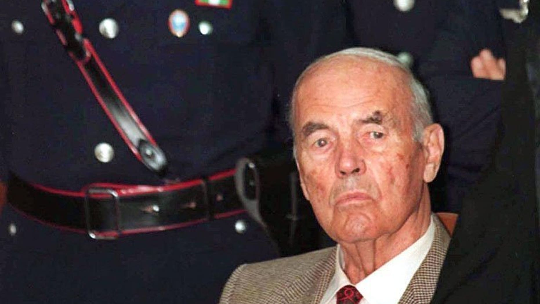 This file picture taken on July 30, 1996 shows former German SS officer Erich Priebke surrounded by police at a military court in Rome. The 100th birthday of Priebke -- one of the last Nazi criminals alive -- has sparked calls for a public apology from relatives of his victims 69 years after their murder and resentment over his freedom of movement.