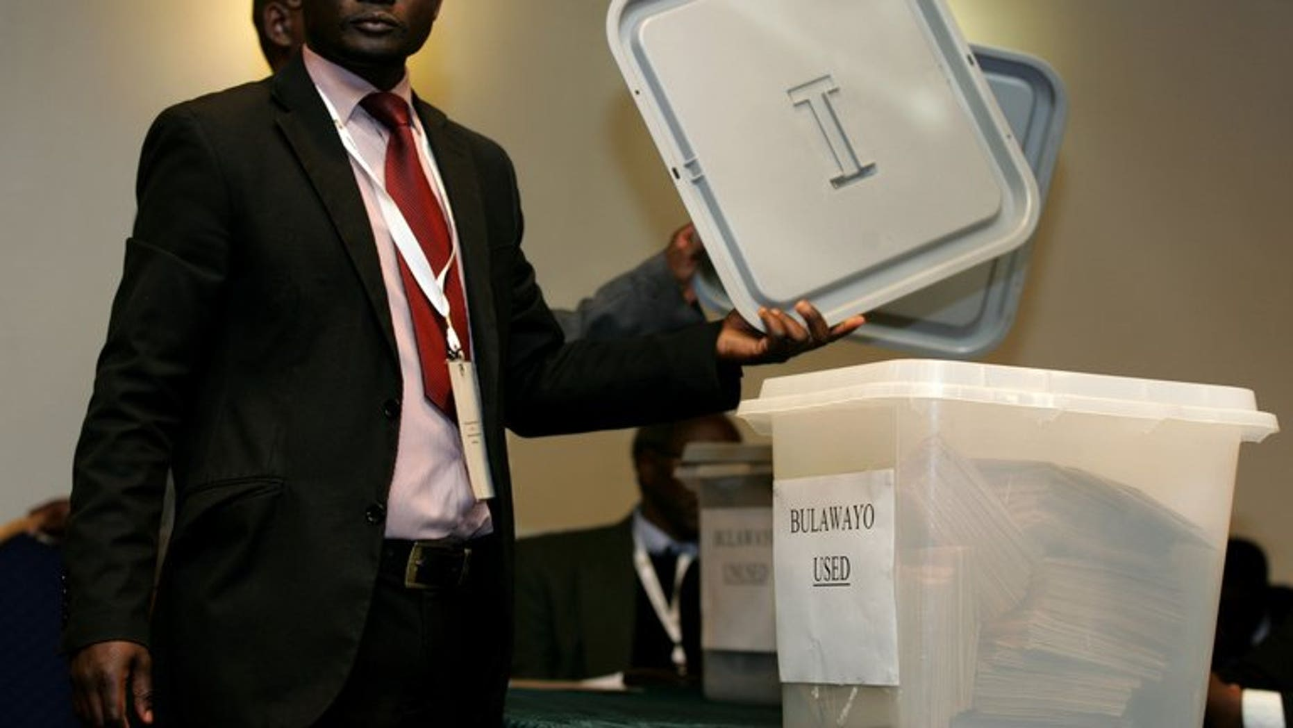 An official from the Zimbabwe Electoral Commission (ZEC) shows a lid before sealing a ballot box in harare on July 19, 2013. Zimbabwe election authorities insisted Tuesday that they would be ready to hold general elections in a week's time, despite fears of vote rigging and a lack of funding.
