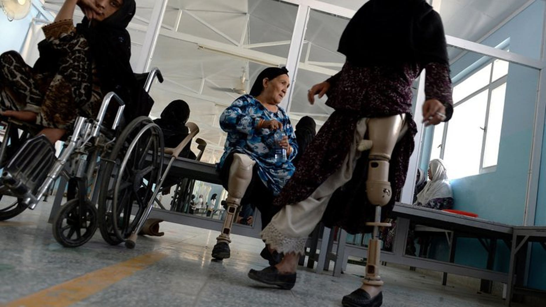 An Afghan amputee practices walking with her prosthetic leg at one of the International Committee of the Red Cross (ICRC) hospitals for war victims and the disabled in Kabul June 5, 2013. The Red Cross said Tuesday it will shut down three of its 17 offices in Afghanistan, two months after an unprecedented militant attack on the organisation.