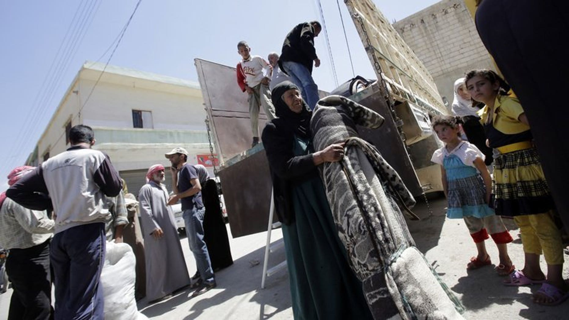A Syrian woman carries her belongings upon her arrival in the Bekaa valley where she will find shelter, on June 14, 2013. The Lebanese government has imposed new entry controls on Syrians in a bid to reduce friction between the host population and the 600,000 who have already crossed.