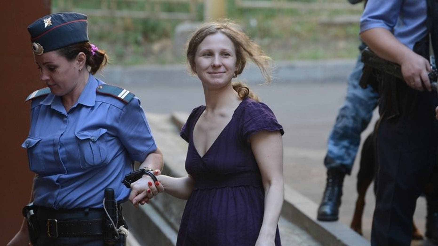 """File picture shows Maria Alyokhina, a member of punk band """"Pussy Riot,"""" being escorted into court in Moscow on August 8, 2012. Alyokhina on Wednesday asked again to be released on parole after serving almost a year in prison for a protest againt President Vladimir Putin in a Moscow church."""