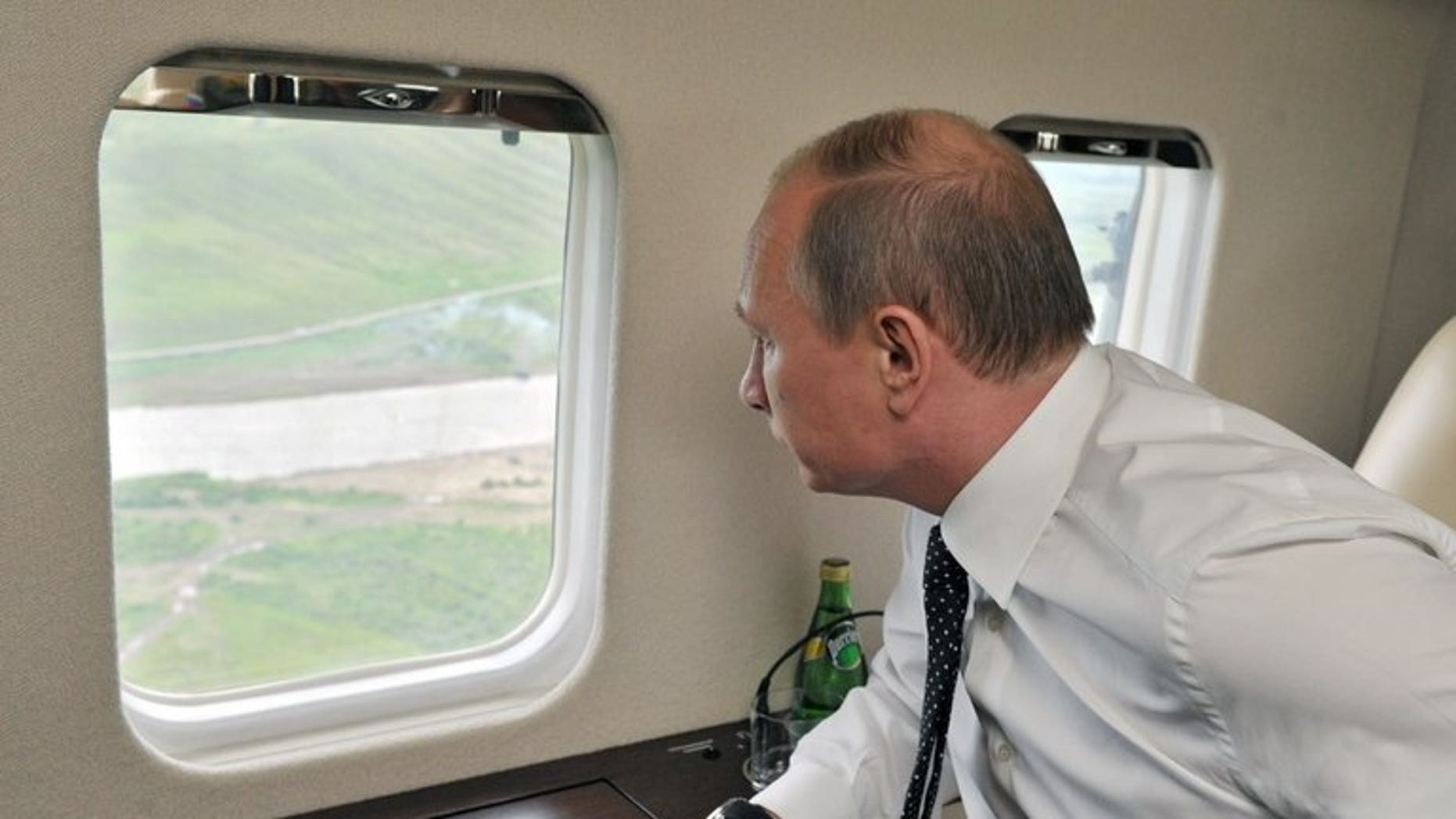 Russian President Vladimir Putin watches military exercises from a plane near the eastern Siberian city of Chita on July 17, 2013. President Vladimir Putin is to visit Iran in August to try and restart talks on Tehran's controversial nuclear programme, Russia's Kommersant daily reported on Wednesday.