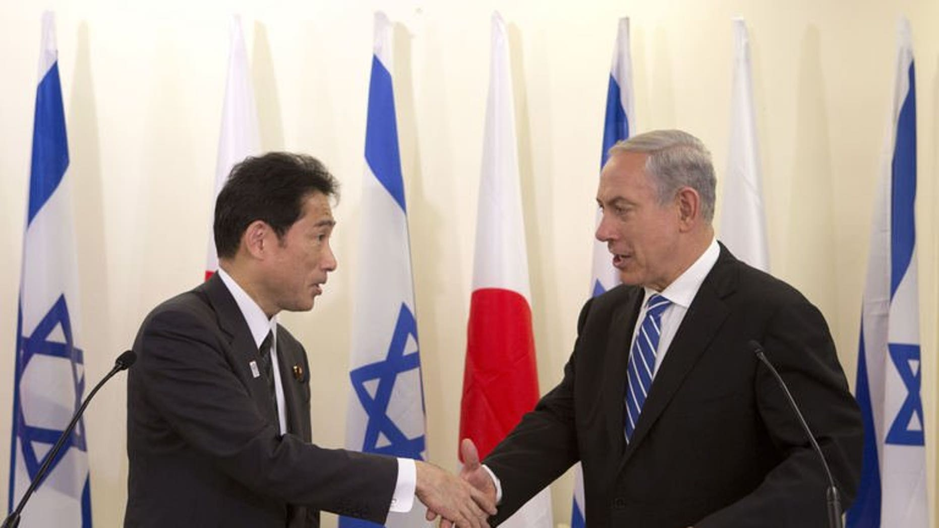 Japanese Foreign Minister Fumio Kishida (left) shakes hands with Israeli Prime Minister Benjamin Netanyahu during a joint press conference in Jerusalem, on July 24, 2013. Netanyahu has urged greater pressure on Iran over its nuclear programme as he met Kishida.