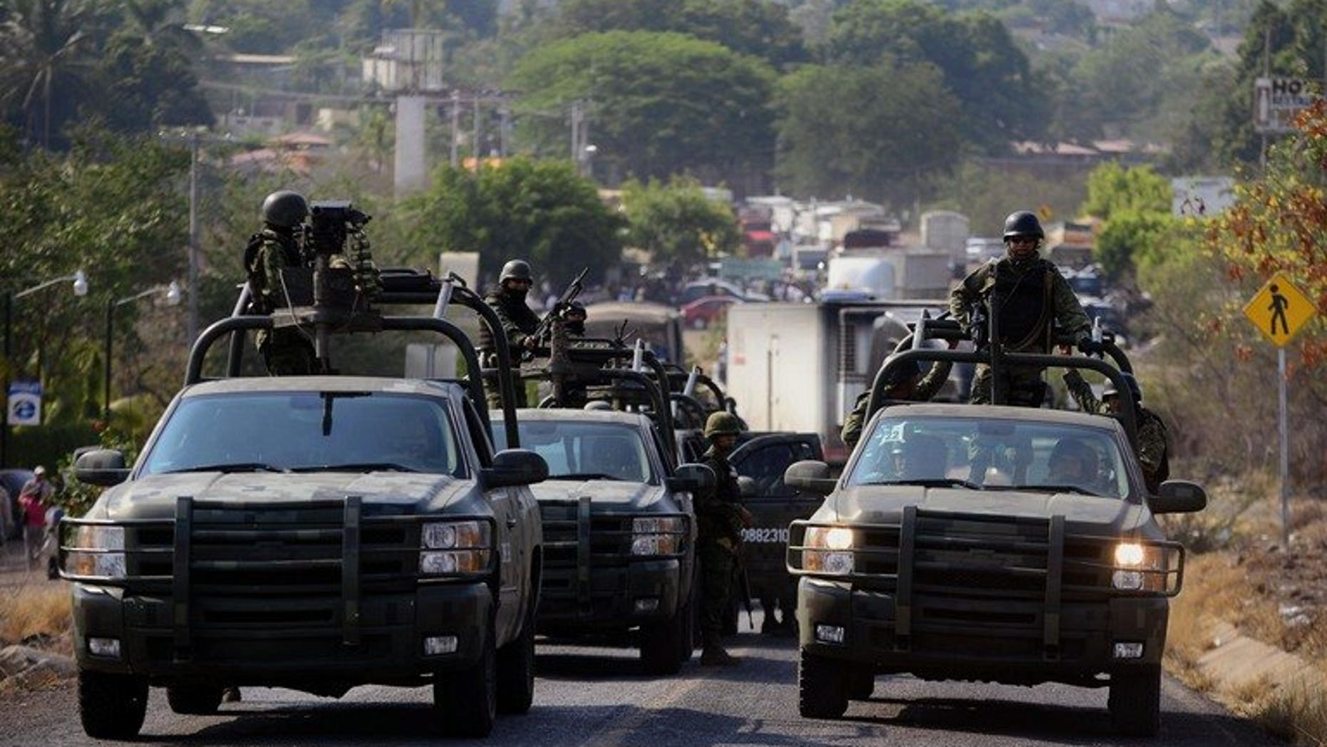 Soldiers of Mexican Army patrol in Michoacan State, Mexico on May 22, 2013. Security forces in the Mexican state plagued by drug violence were working to restore order on Wednesday after clashes which left 22 dead.