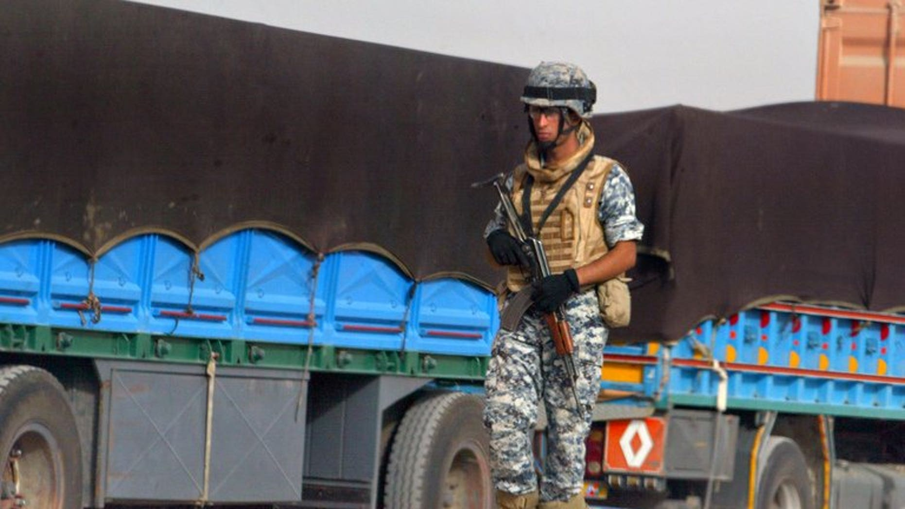 An Iraqi policeman walks past trucks in Amara on June 20, 2008. Gunmen killed 14 truck drivers and stole their vehicles on a highway north of Baghdad on Thursday, while dozens of other militants attacked a nearby town, a local administrative official said.