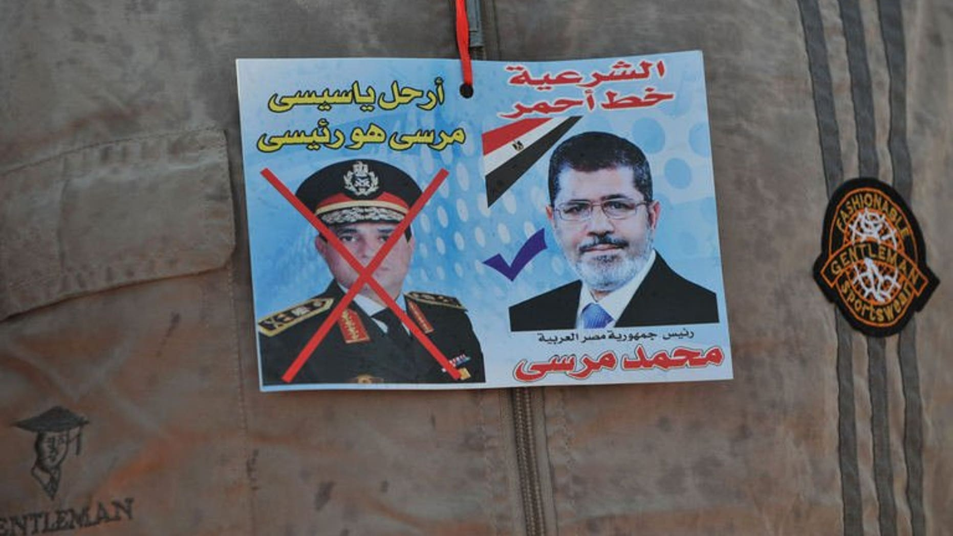 """A sticker on the shirt of a supporter of Egypt's ousted president Mohamed Morsi shows Morsi (R) with text above it reading in Arabic: """"Legitimacy is the red line"""" and one of army chief Abdel Fattah al-Sisi (L) with text above reading in Arabic: """"Leave Sisi, Morsi is the president"""" outside Cairo's Rabaa al-Adawiya mosque on July 24, 2013."""