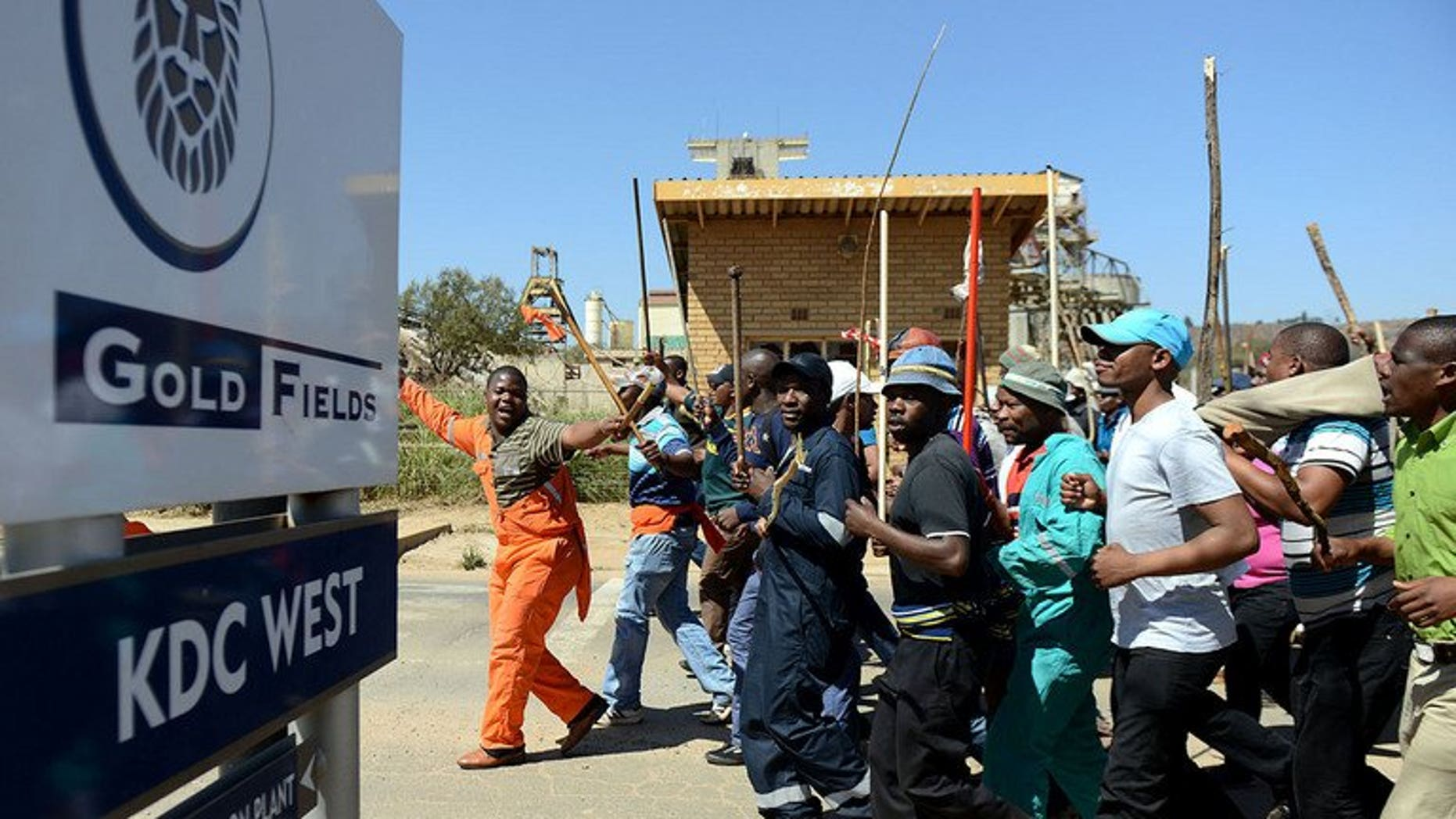 Striking Gold Fields mine workers march on September 11, 2012 in Carletonville, west of Johannesburg. Gold miners have vowed to take their silicosis lawsuit against London-listed Anglo American to South Africa's courts, after a British court refused to hear their case.
