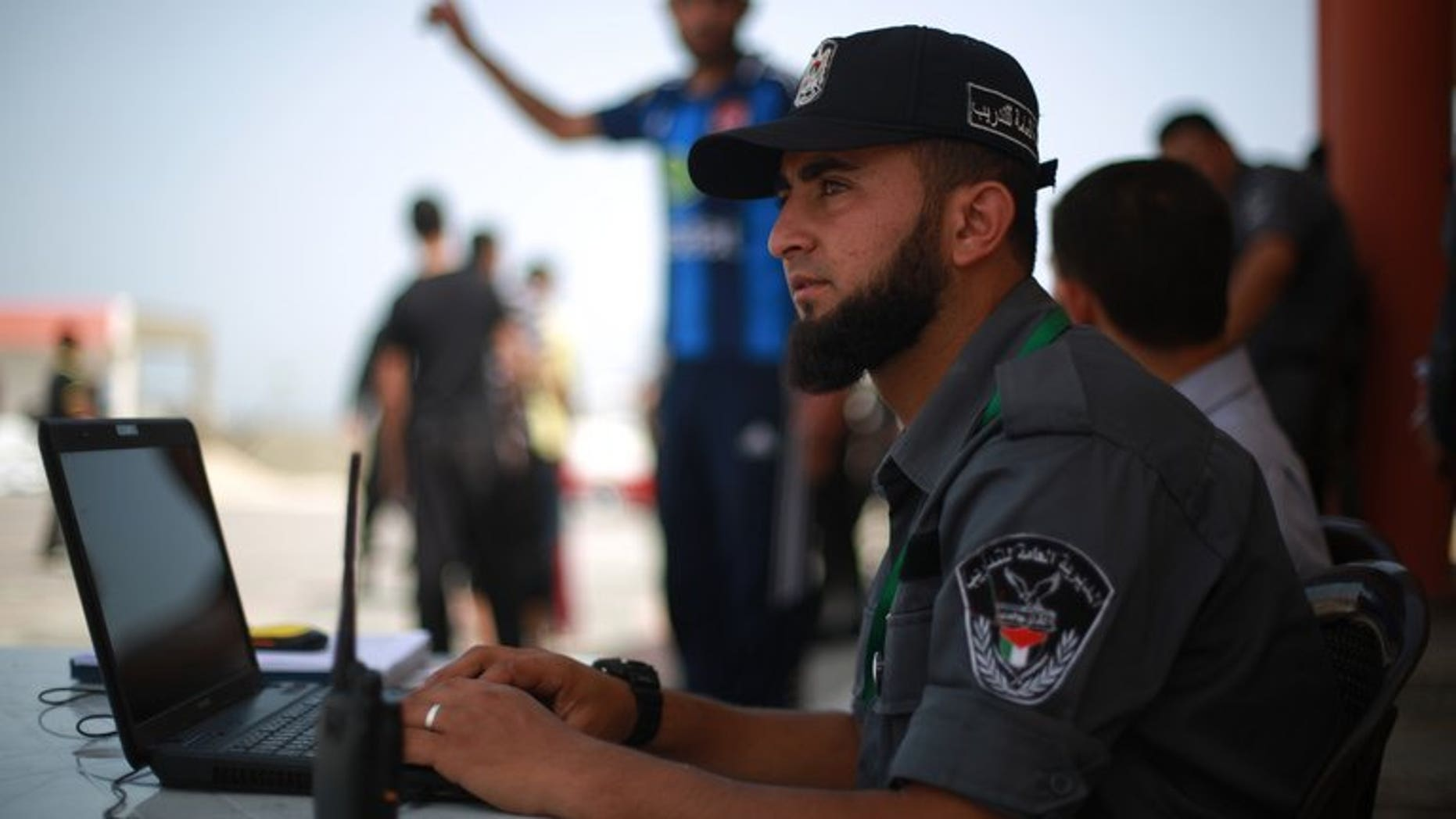"""A Hamas policeman sits at his laptop in Gaza City on June 2, 2013. Authorities in the Hamas-ruled Gaza Strip on Thursday closed local offices of Al-Arabiya TV and Palestinian news agency Maan for alleged """"false"""" reporting of Hamas help for Egypt's Muslim Brotherhood."""