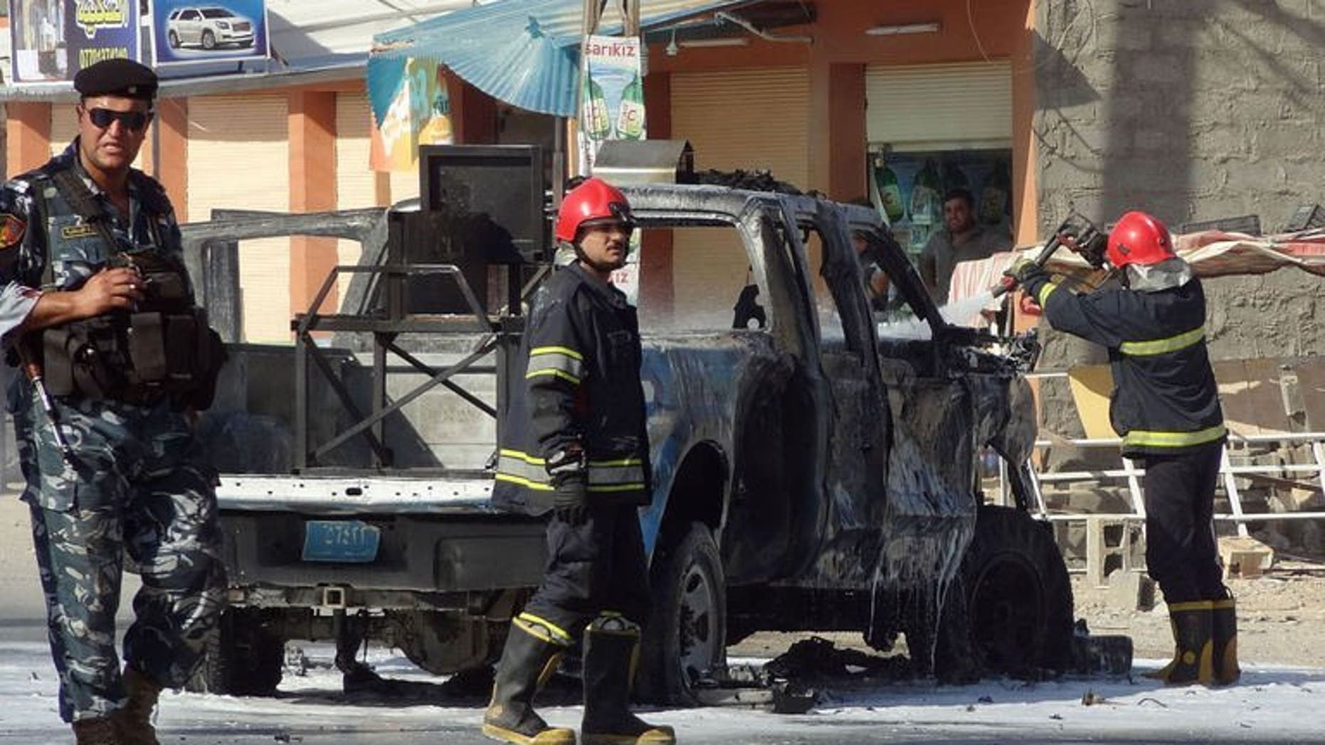Iraqi firefighters extinguish fire from a vehicle at the site of an explosion near the northern city of Kirkuk on July 25, 2013. Bombs exploded near shops and cafes in Iraq on Thursday night, killing at least 17 people, officials said.