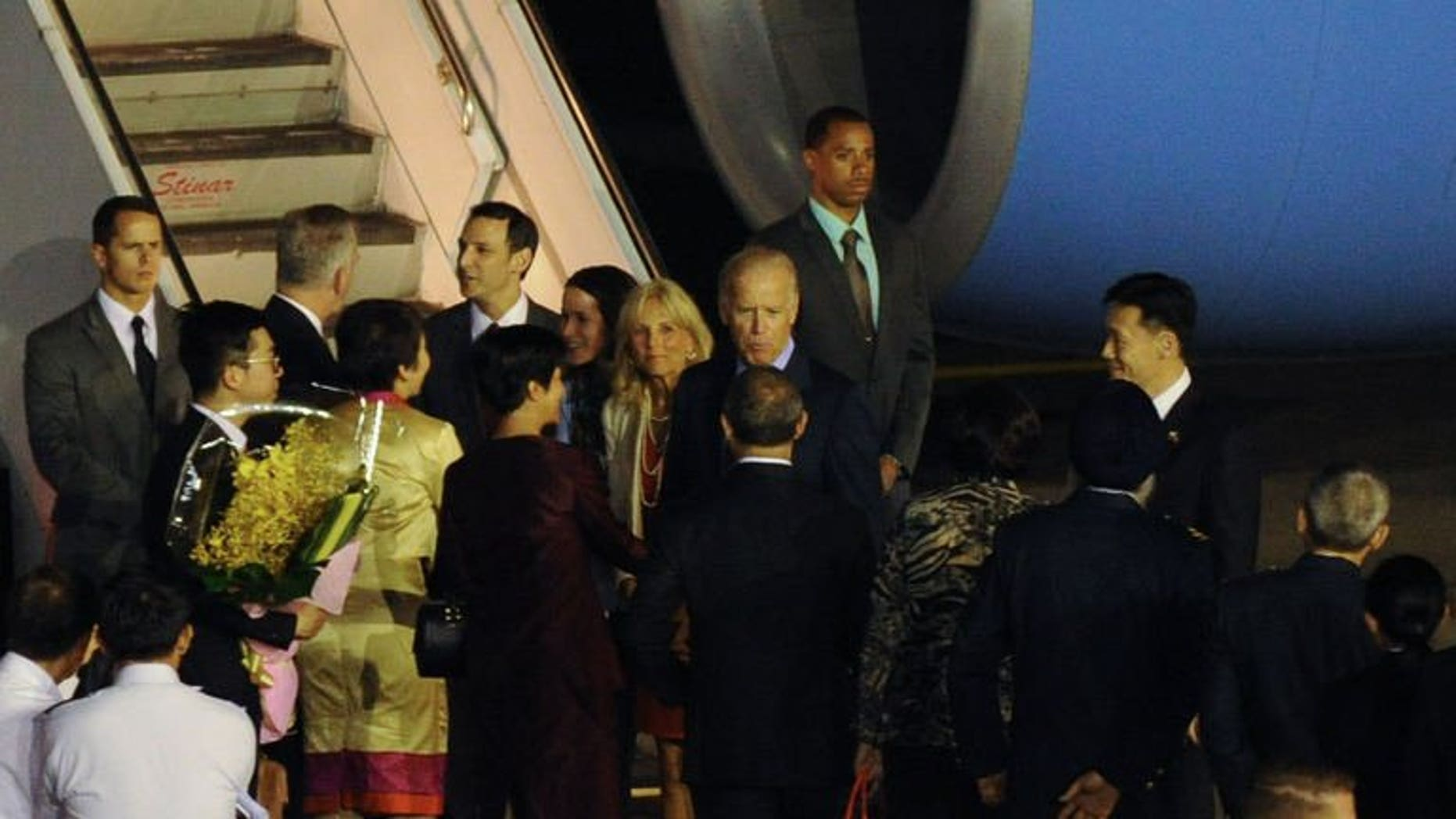US Vice President Joe Biden (centre R) with his wife Jill Biden (centre L) greeted by officials upon arrival at the Paya Lebar military airport in Singapore on July 25, 2013. Biden arrived in Singapore on Thursday for a visit in which he is expected discuss trade ties and ways to calm regional maritime tensions.