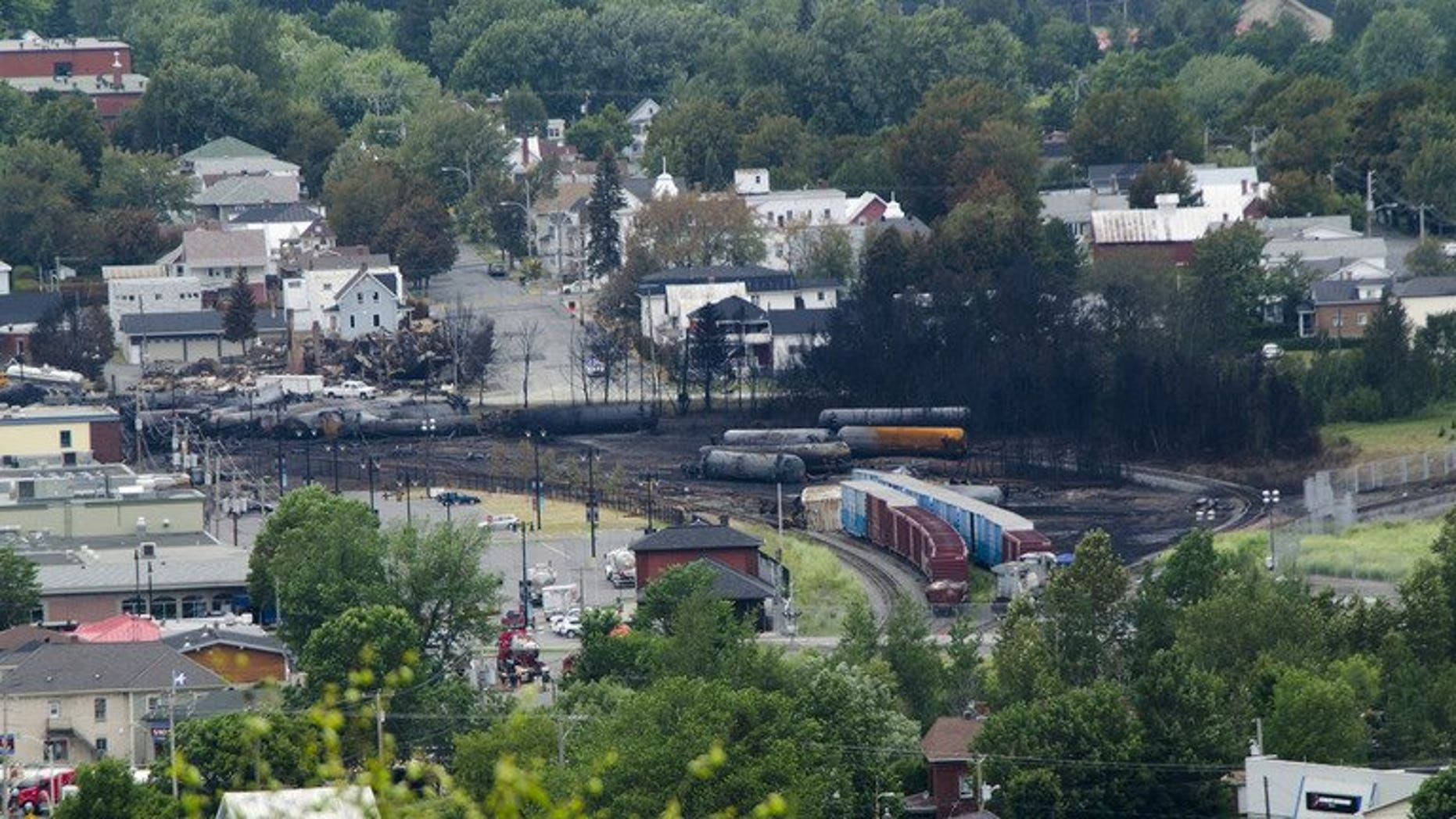 Scorched oil tankers remain on July 10, 2013 at the train derailment site in Lac-Megantic, Quebec. Police on Thursday raided the Canadian regional office of the Montreal, Maine & Atlantic (MMA) railway, looking for evidence in a criminal investigation of a train derailment that killed 47 people.
