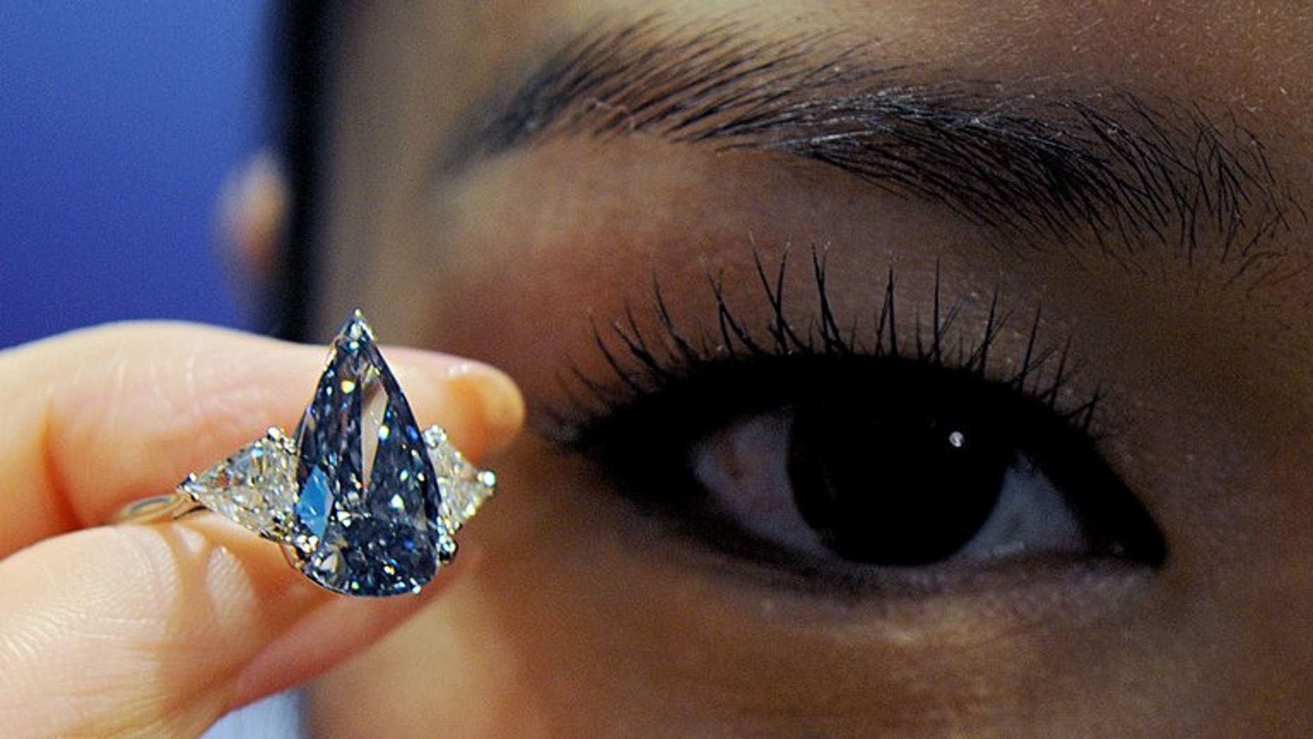 """A model holds a 'De Beers Millennium Blue Diamond' valued at an estimated $ 4.6-5.9 mn in Hong Kong in 2010. The world's top diamond producer De Beers on Friday reported """"steady"""" total first-half sales of $3.3 billion (2.5 billion euros), unchanged from the outcome in the first half of 2012."""