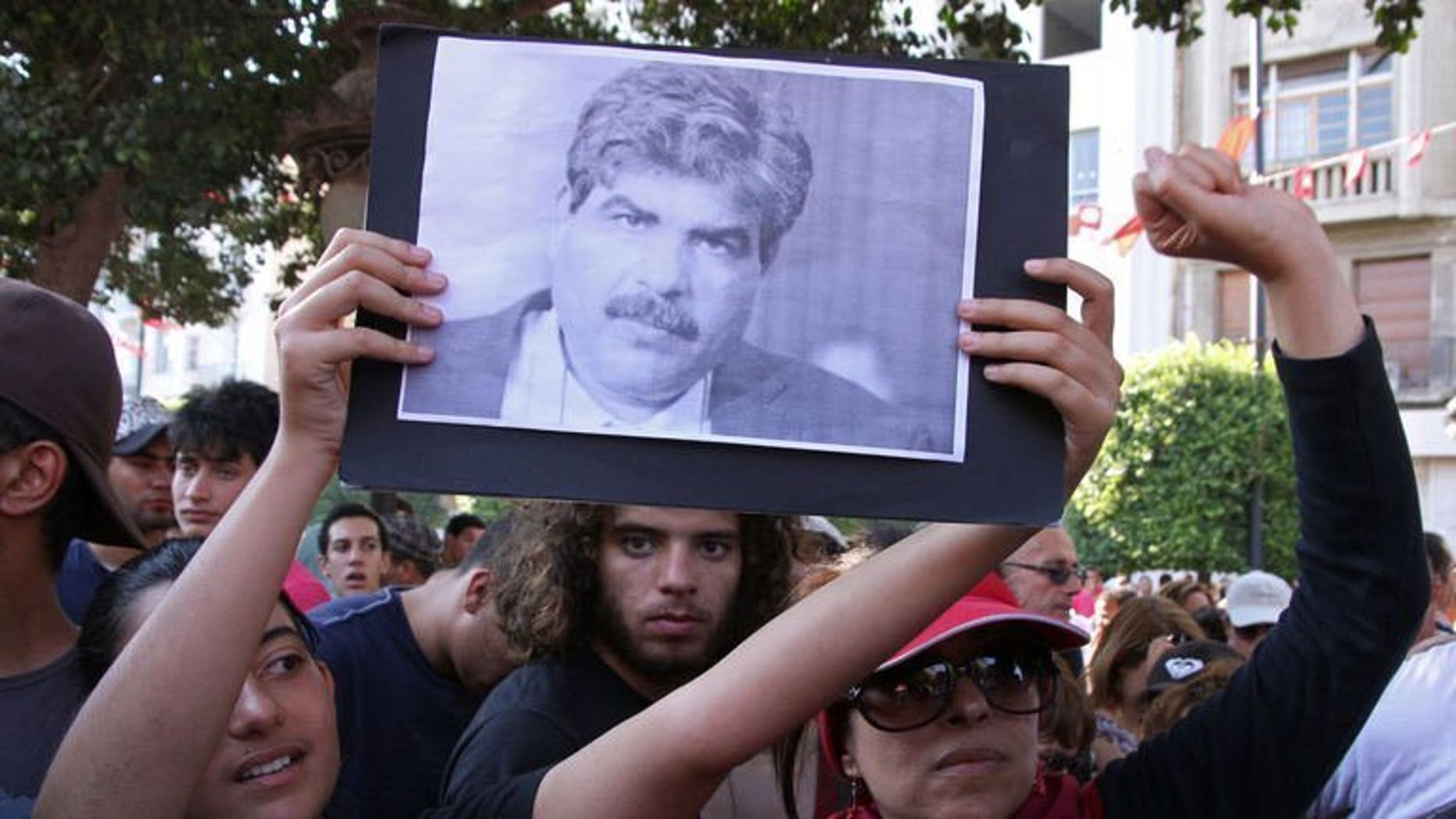 Tunisians hold a portrait of slain opposition politician Mohamed Brahmi on July 25, 2013. Tunisian Interior Minister Lotfi Ben Jeddou has said that Brahmi was killed with the same weapon as fellow opposition figure Chokri Belaid.