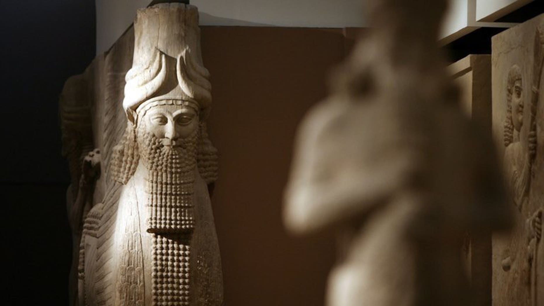 A statue is lit by natural light inside the Assyrian Hall of the Iraqi National Museum on September 21, 2010. Some 15,000 artefacts were stolen from the national museum in Baghdad by looters in the chaos that followed the 2003 US-led invasion of Iraq. Baghdad reached an initial deal with the US on the return of more than 10,000 artefacts stolen from Iraq after the 2003 US-led invasion.