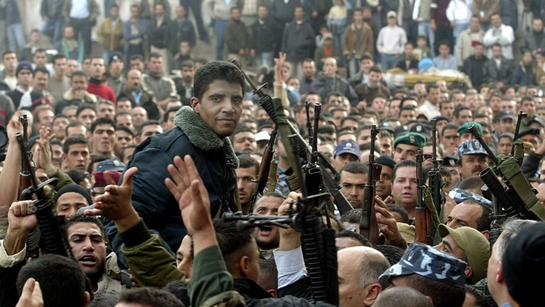 Palestinian militant leader Zakaria Zubeidi (center) and supporters take part in a rally in the West Bank town of Jenin on December 30, 2004. Zubeidi's brother, Daoud Zubeidi, was arrested by Israeli security forces on Friday, Palestinian security forces said.