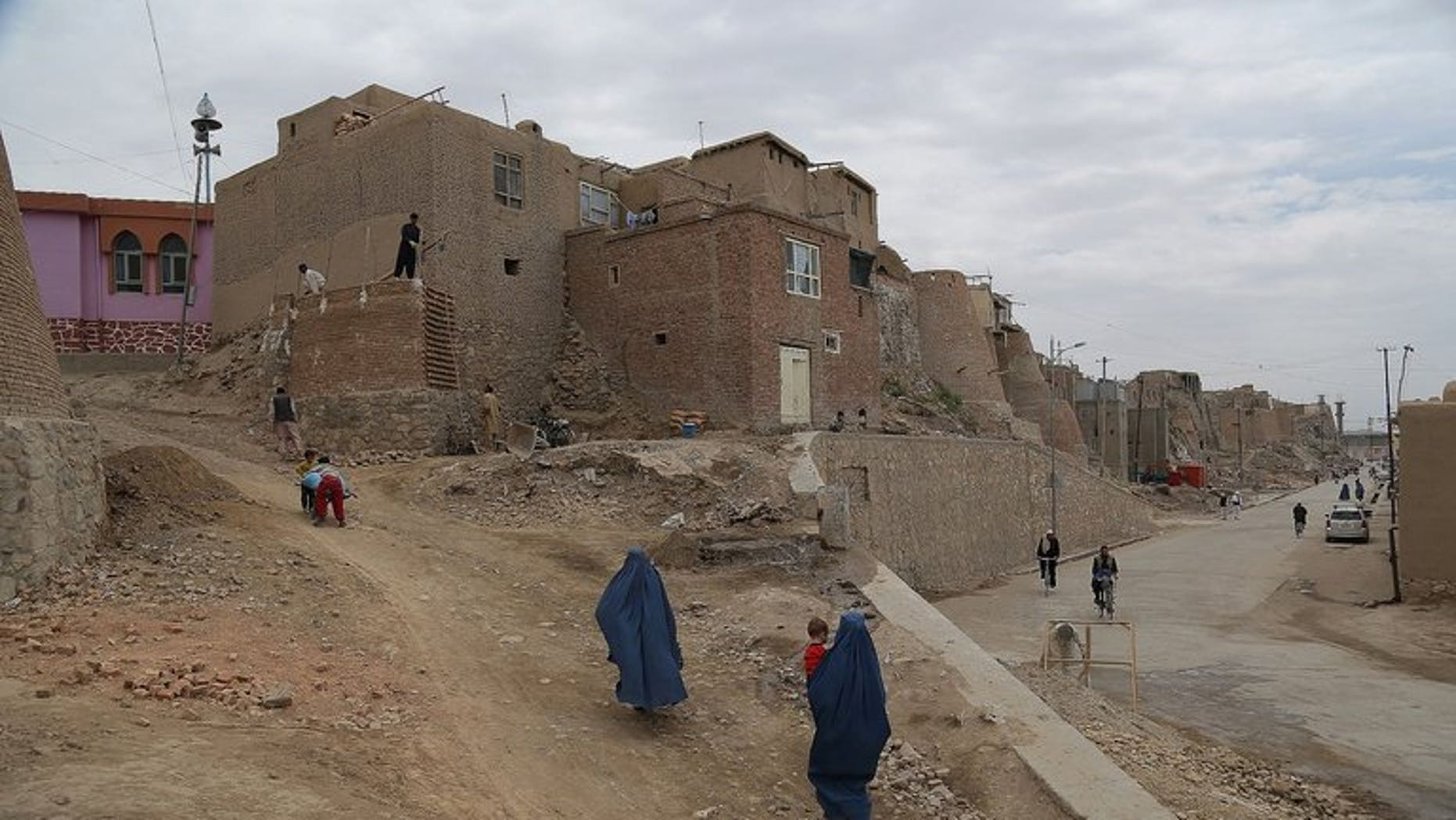 Afghan residents walk in a section of the old city in Ghazni province on June 30, 2013. A suicide bomber on a motorcycle struck a busy marketplace in the area, killing at least seven people including an anti-Taliban militia leader, officials said.