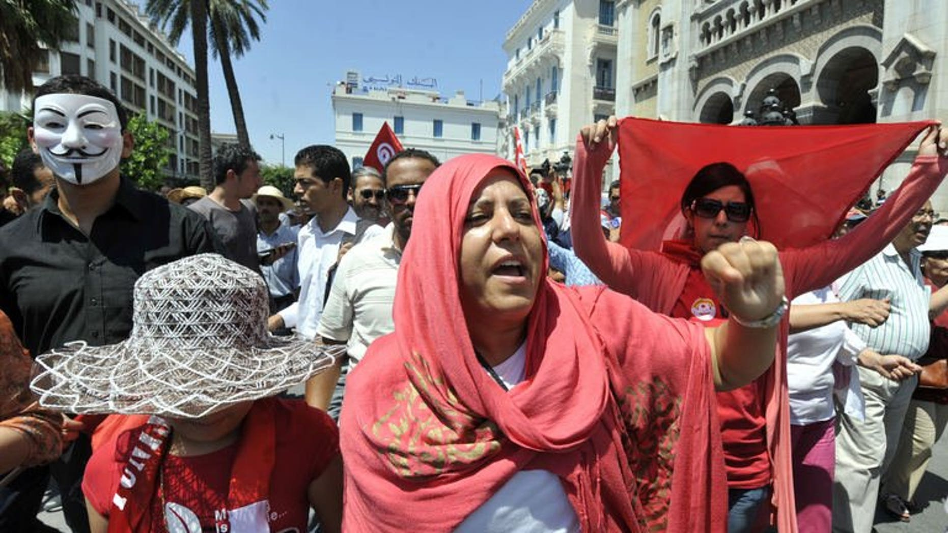 Tunisian protesters shout slogans during an anti-government demonstration on July 26, 2013 in Tunis after the killing of the opposition politician Mohamed Brahmi. A demonstrator was killed in the central Tunisian town of Gafsa overnight during a march protesting the assassination of Brahmi.