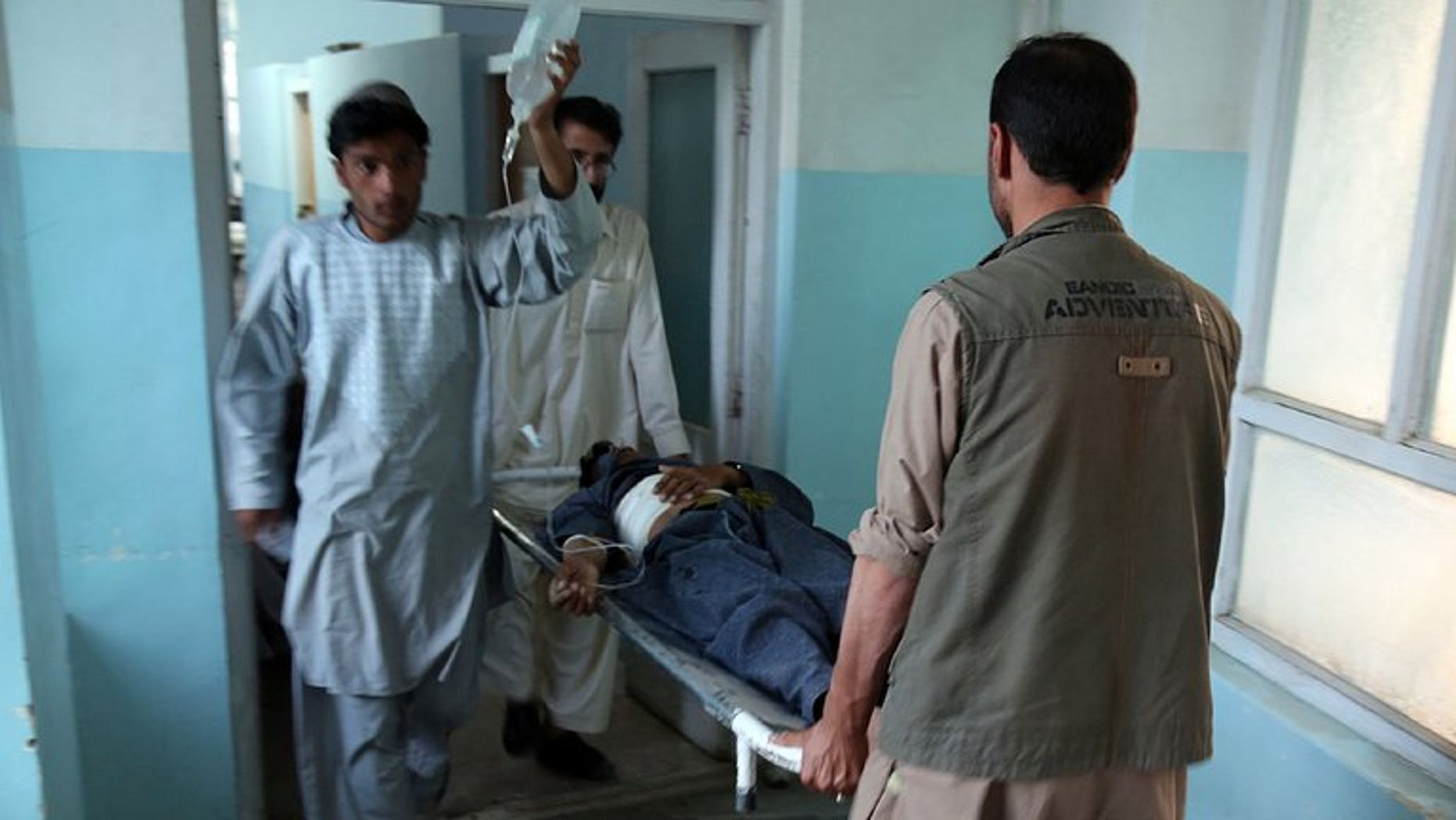 Medical staff carry a wounded man at the main hospital in Ghazni after a suicide attack in Qara Bagh district, on July 26, 2013. A suicide bomber riding a motorcycle struck a busy marketplace and killed seven people, including an anti-Taliban militia leader.