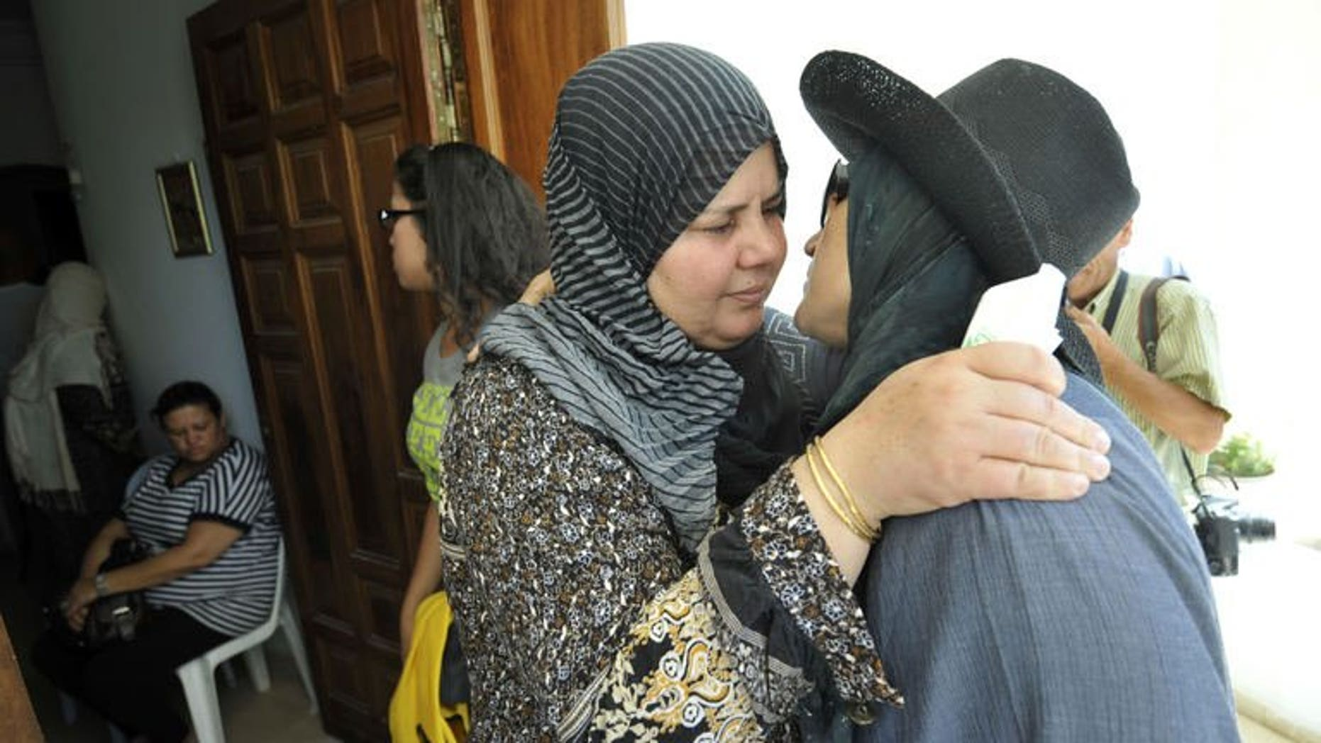 Mubarka Brahmi (centre), the wife of slain opposition politician Mohamed Brahmi, receives condolences from Tunisians at her house in Ariana,Tunisia on July 25, 2013. The politician's funeral procession left his home under military escort on Saturday.