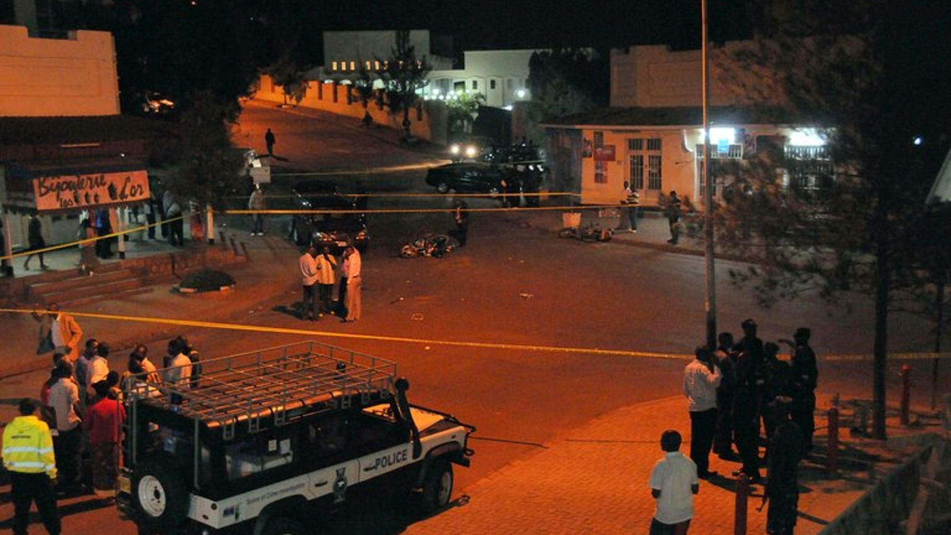 Rwanda National Police forensic officers examine the site of a grenade blast in the city-center of Kigali on March 30, 2012. A grenade attack in the Rwandan capital Kigali killed three people, police said Saturday, after a third victim succumbed to his injuries.