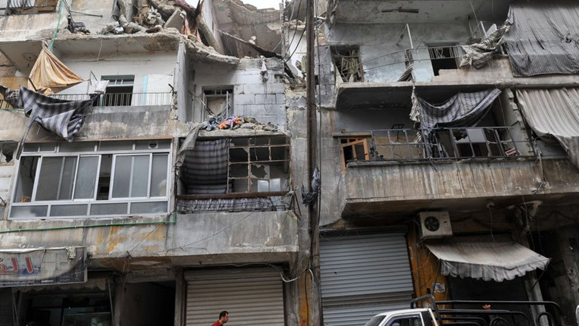 Syrians walk past a partially destroyed building in the northern city of Aleppo on March 22, 2013. At least 29 people, including 19 children, died in a missile strike by regime forces on the northern Syrian city of Aleppo, a watchdog said Saturday, revising an earlier toll.