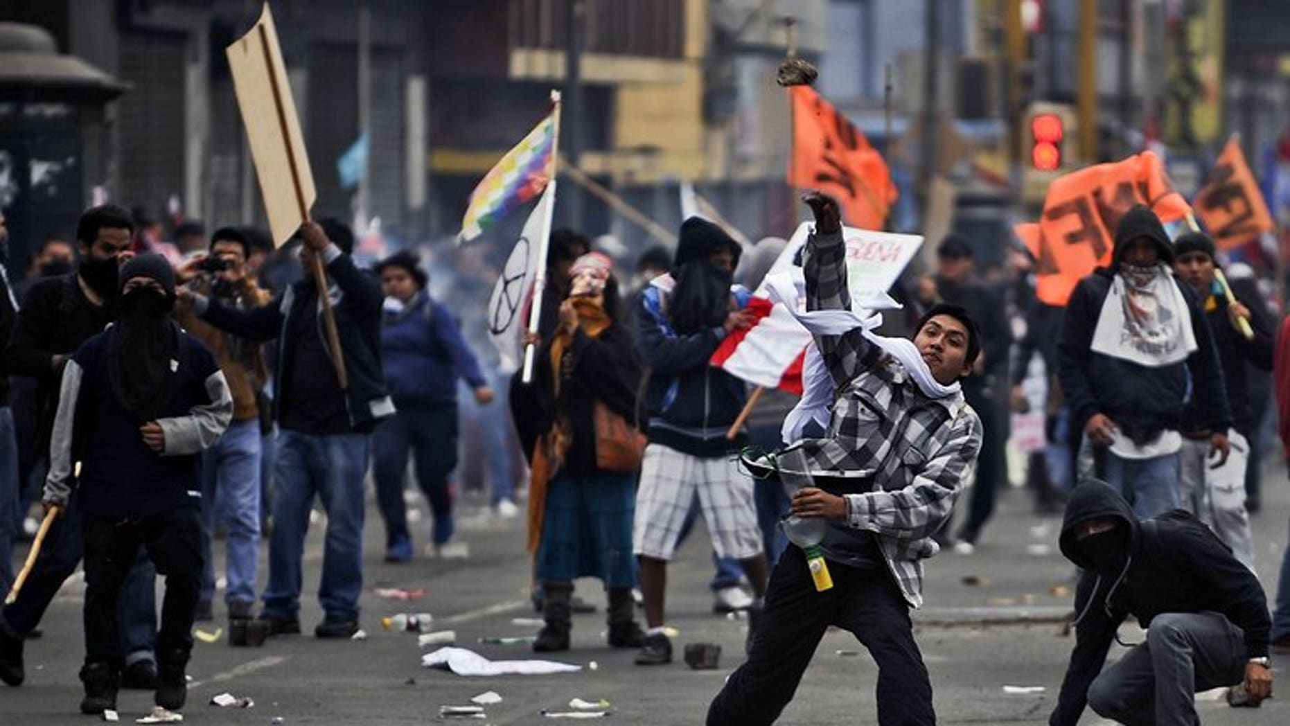 Demonstrators throw stones at riot police in Lima on July 27, 2013. Peruvian police used tear gas and water cannon to drive back thousands of demonstrators protesting against what they said were President Ollanta Humala's failed promises on schools and jobs.
