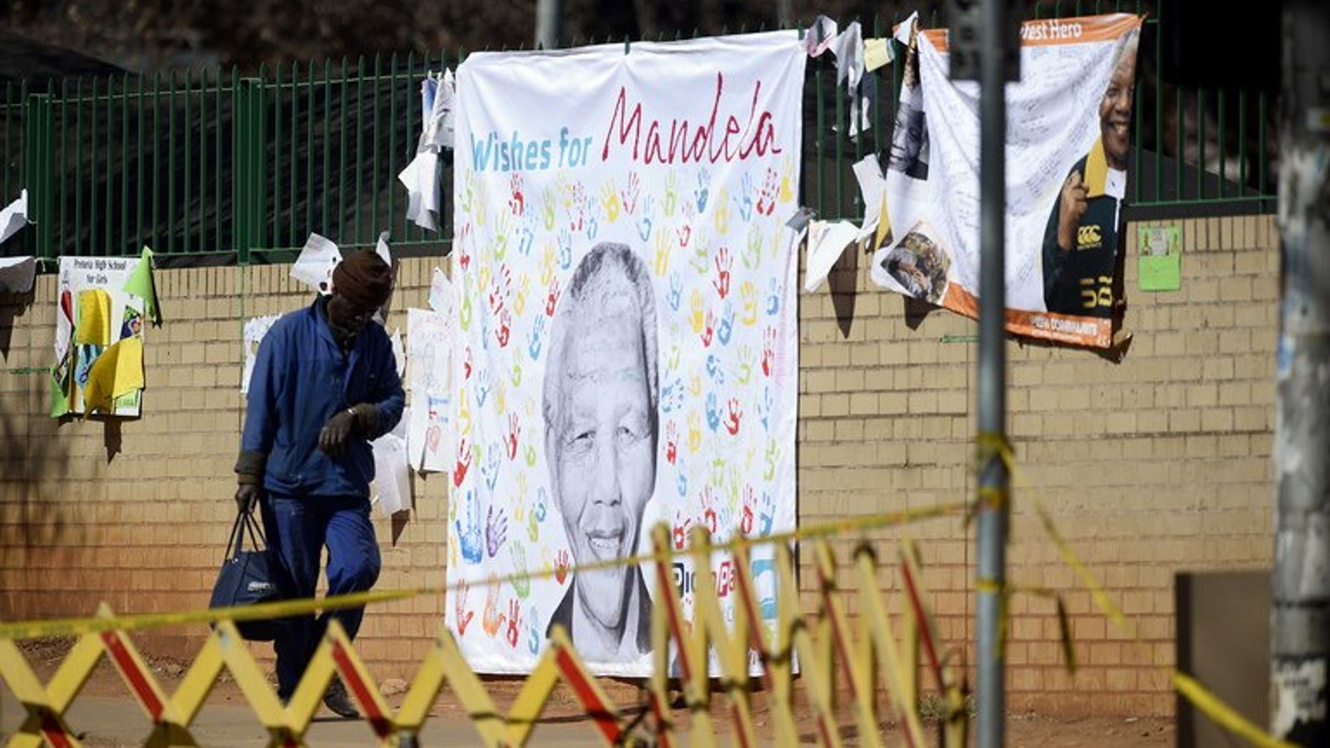 A banner with well-wishing messages left for former South African president Nelson Mandela, on July 19, 2013, outside the Pretoria hospital where he is in a critical condition. South Africa's presidency declined to comment on a report the anti-apartheid hero had undergone an operation.