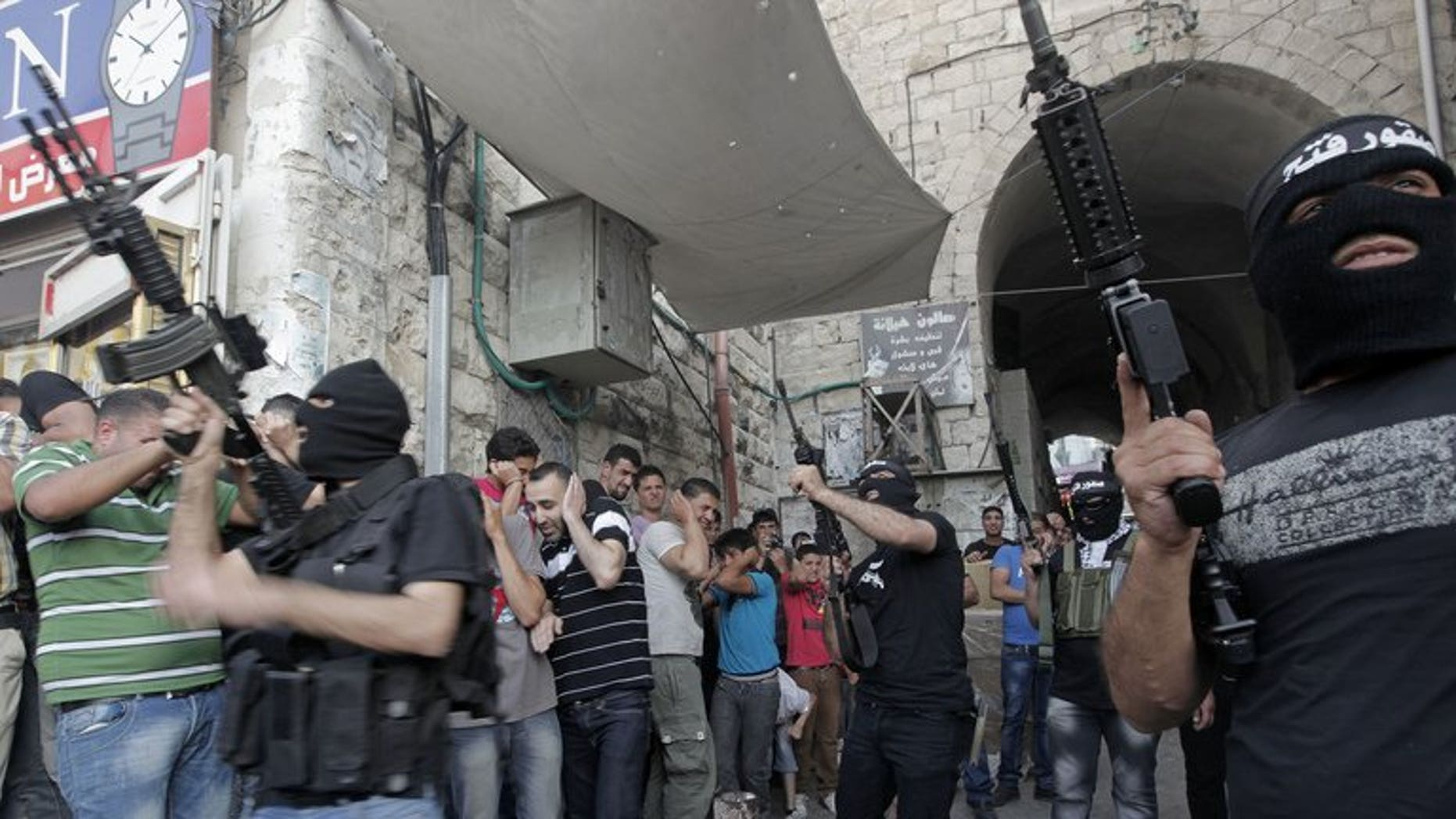 Militants of Al-Aqsa Martyrs' Brigade fire celebratory shots during a ceremony for group member Jamal Nablusi in the West Bank city of Nablus on June 2, 2013 following his release from Israeli prison after serving eight years. As negotiators headed to Washington for the resumption of peace talks on Monday, most Israeli newspapers hit out at the decision to free 104 prisoners in return.