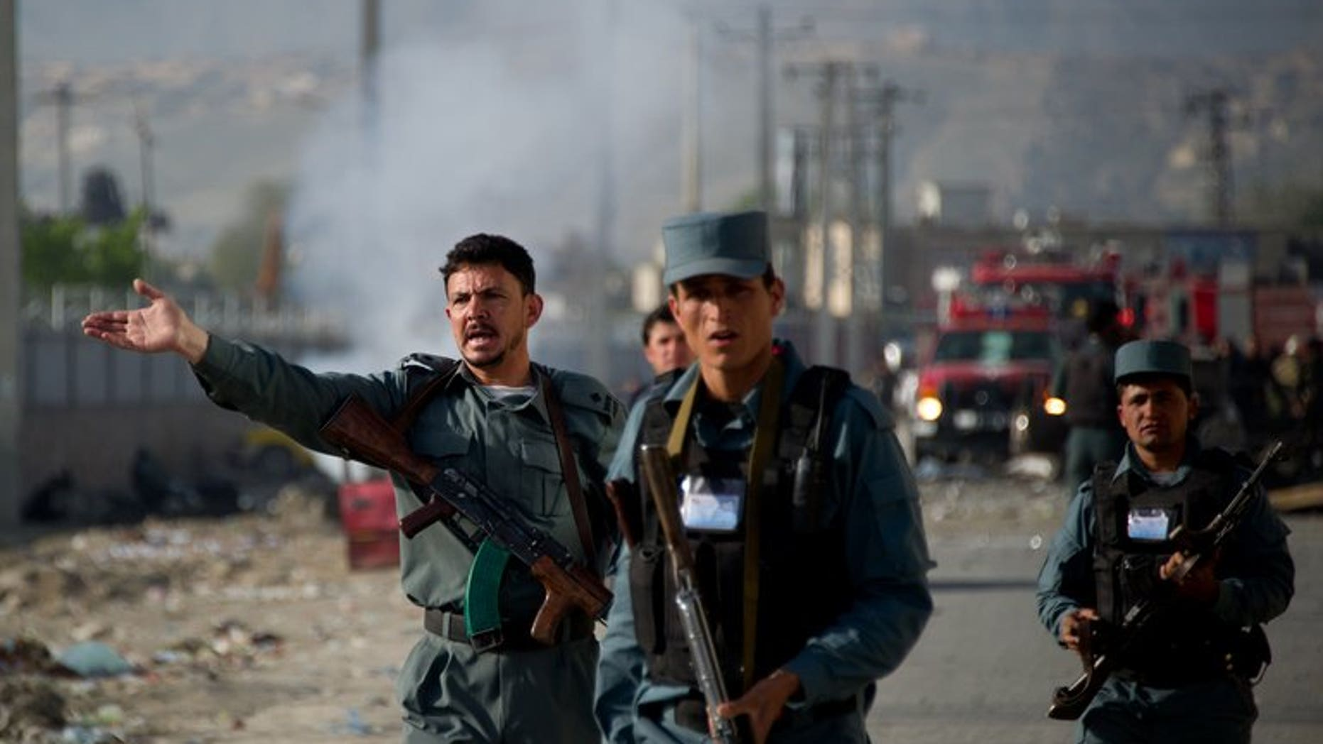 Afghan police personnel gesture as they evacuate onlookers from the site of a suicide bomb attack in Kabul on May 2, 2012. A roadside bomb blamed on the Taliban tore through a police vehicle in southern Afghanistan at the weekend, killing nine people and wounding 15, officials said on Monday.